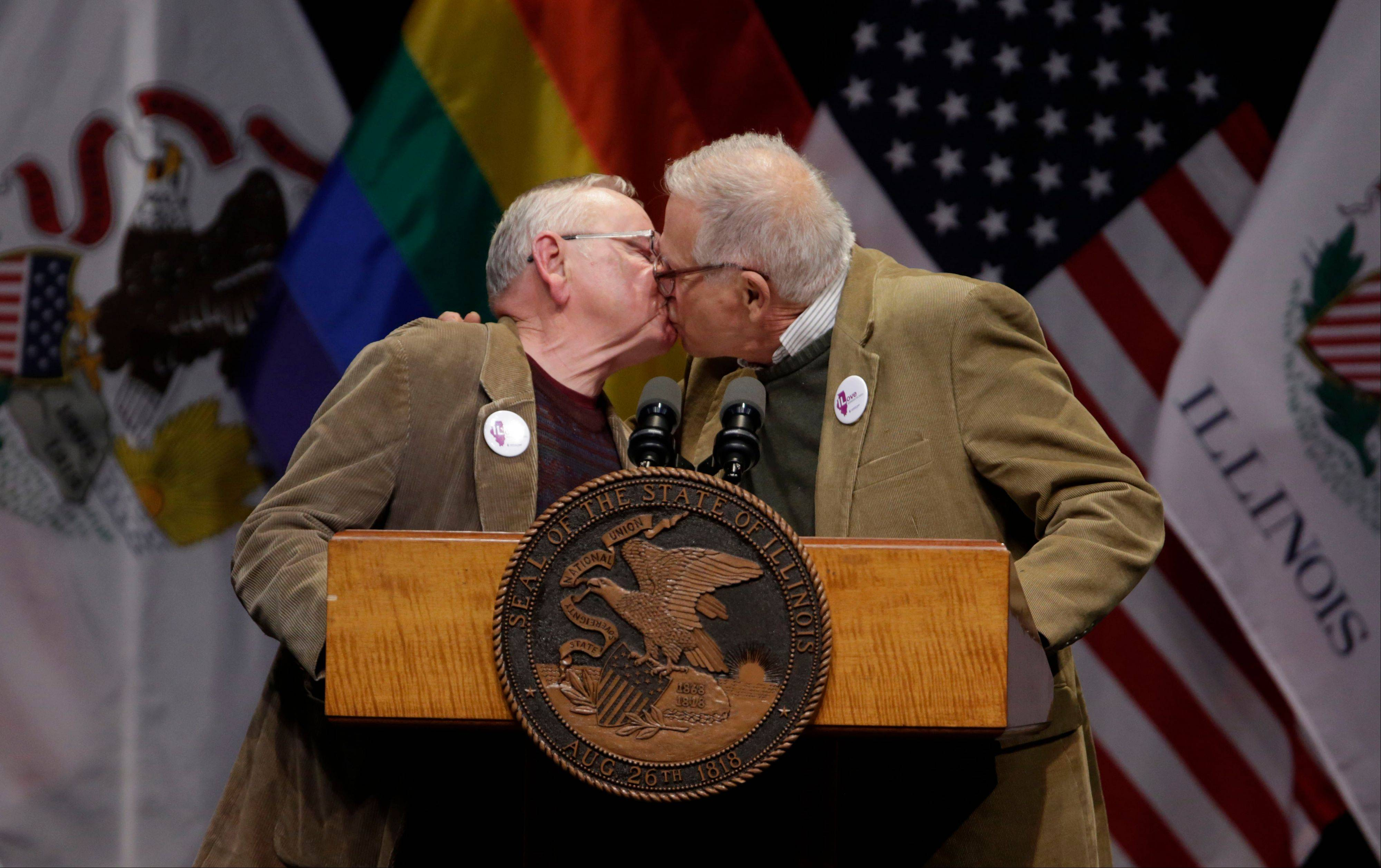 Lifelong partners Jim Darby, left, and Patrick Bova kiss before Illinois Gov. Pat Quinn signed the Religious Freedom and Marriage Fairness Act into law. Darby and Bova have been together for 50 years and now plan to marry in Illinois.