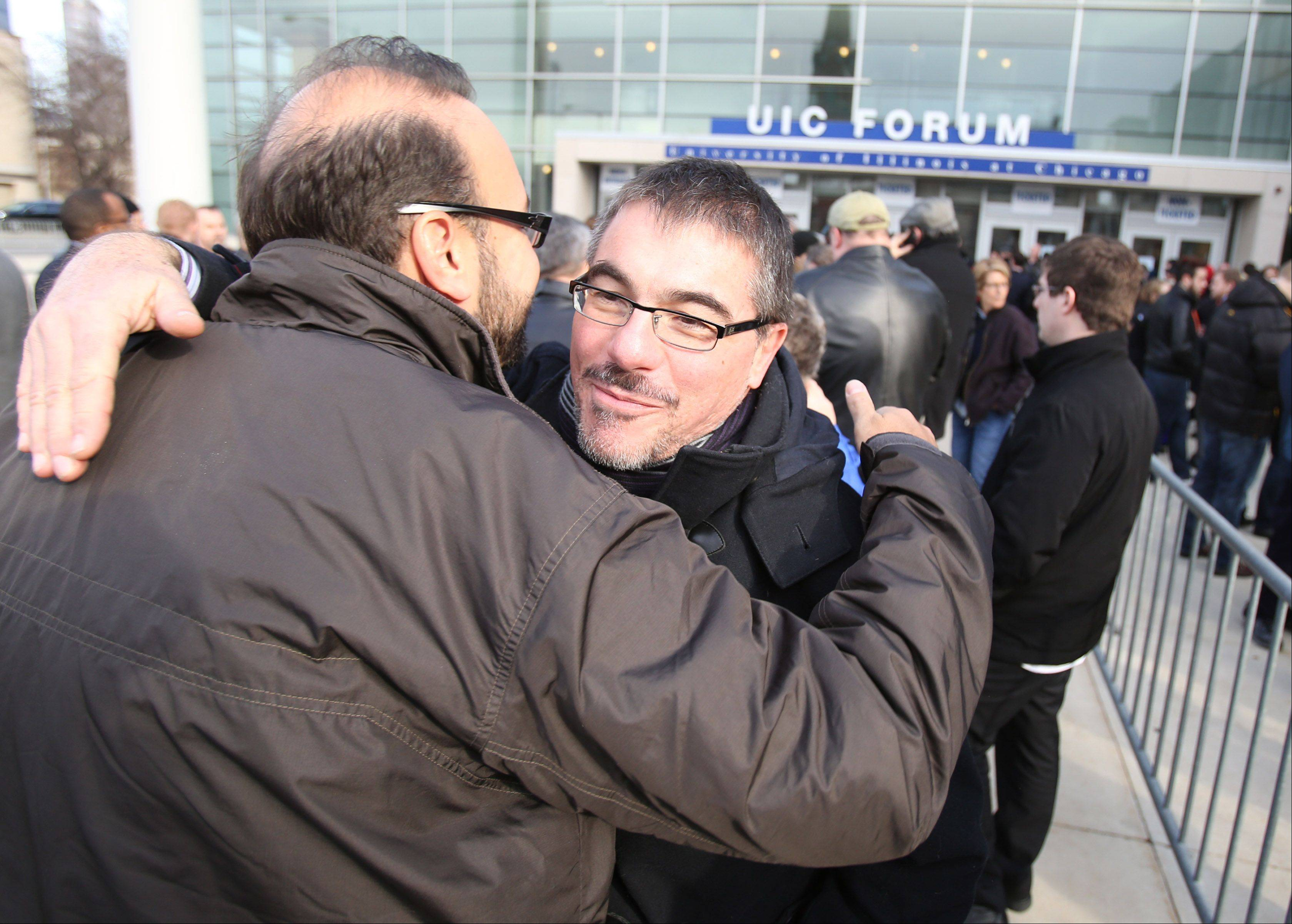 Trevor Slom of Chicago ,right, gets a hug from friend Jeffrey Ciolino of Chicago in front of the UIC Forum before the event.