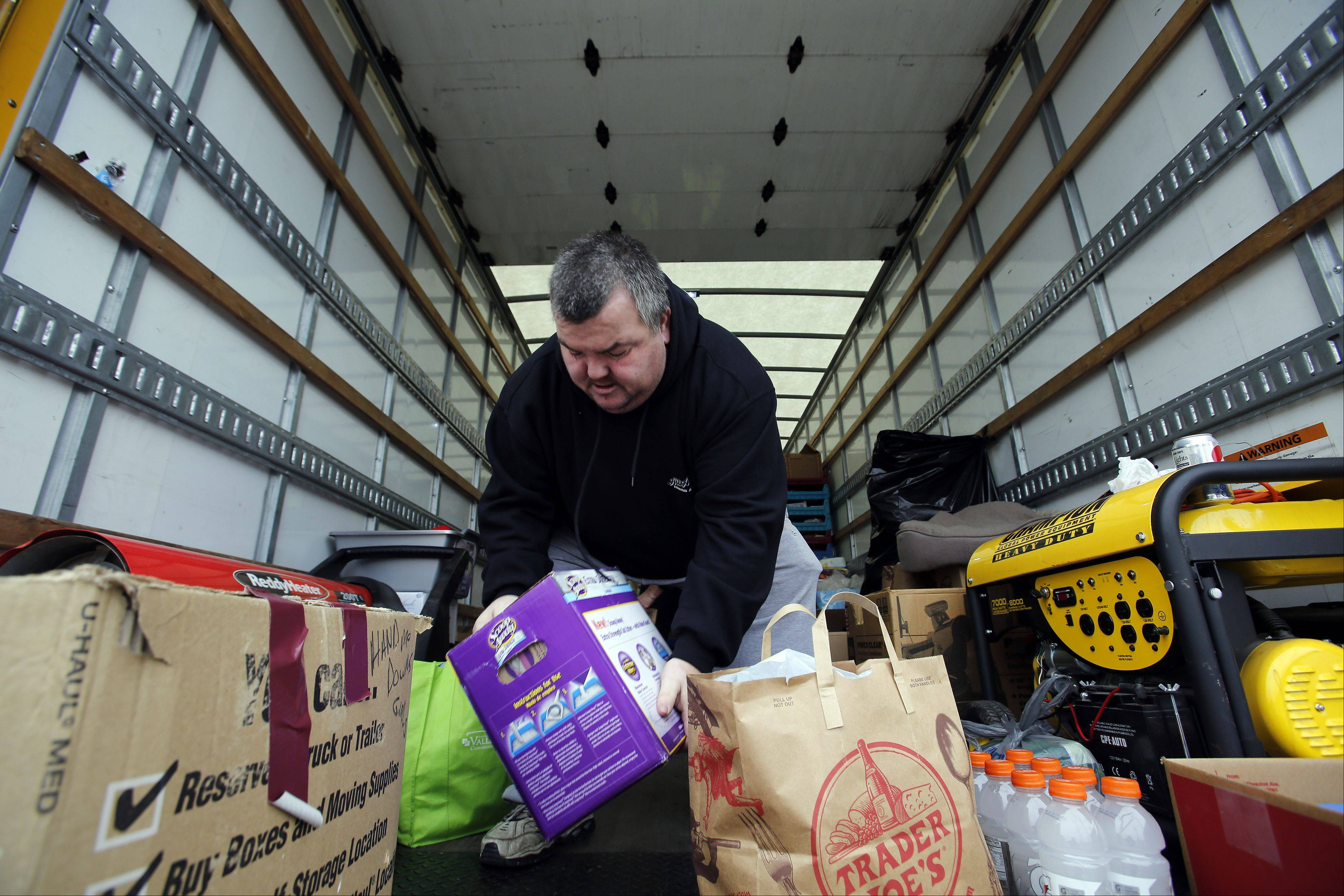 Mike Lyp, owner of All Around Towing & Auto, loads up a large rental truck in Huntley Wednesday with donations for the areas devastated by the recent tornadoes. The Lake in the Hills resident leaves for Washington, Ill., at 4:30 a.m. Thursday to make the first delivery.