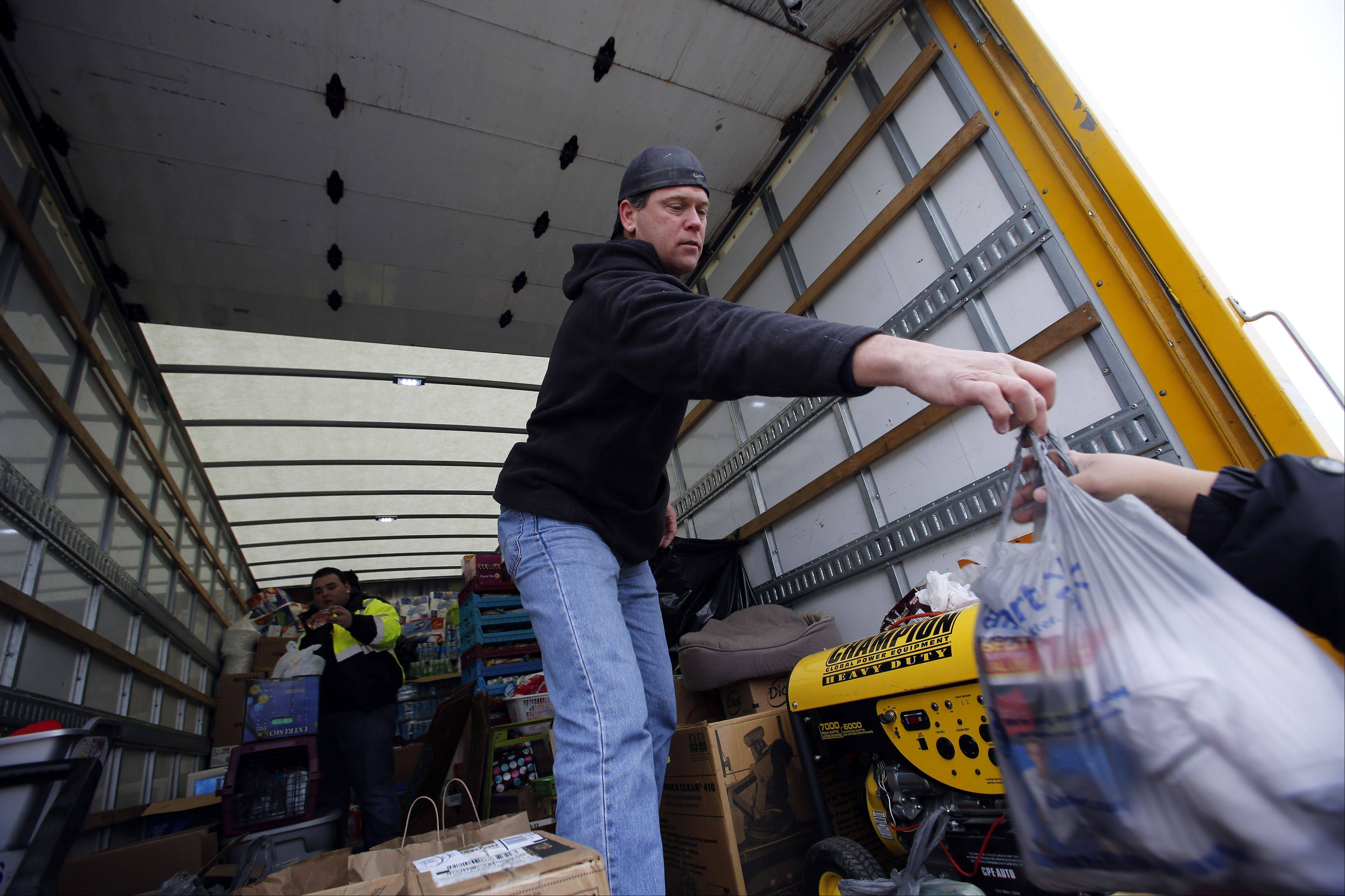 Craig Consoer of Lake in the Hills helps load a truck bound for Washington, Ill., with donations from the area.