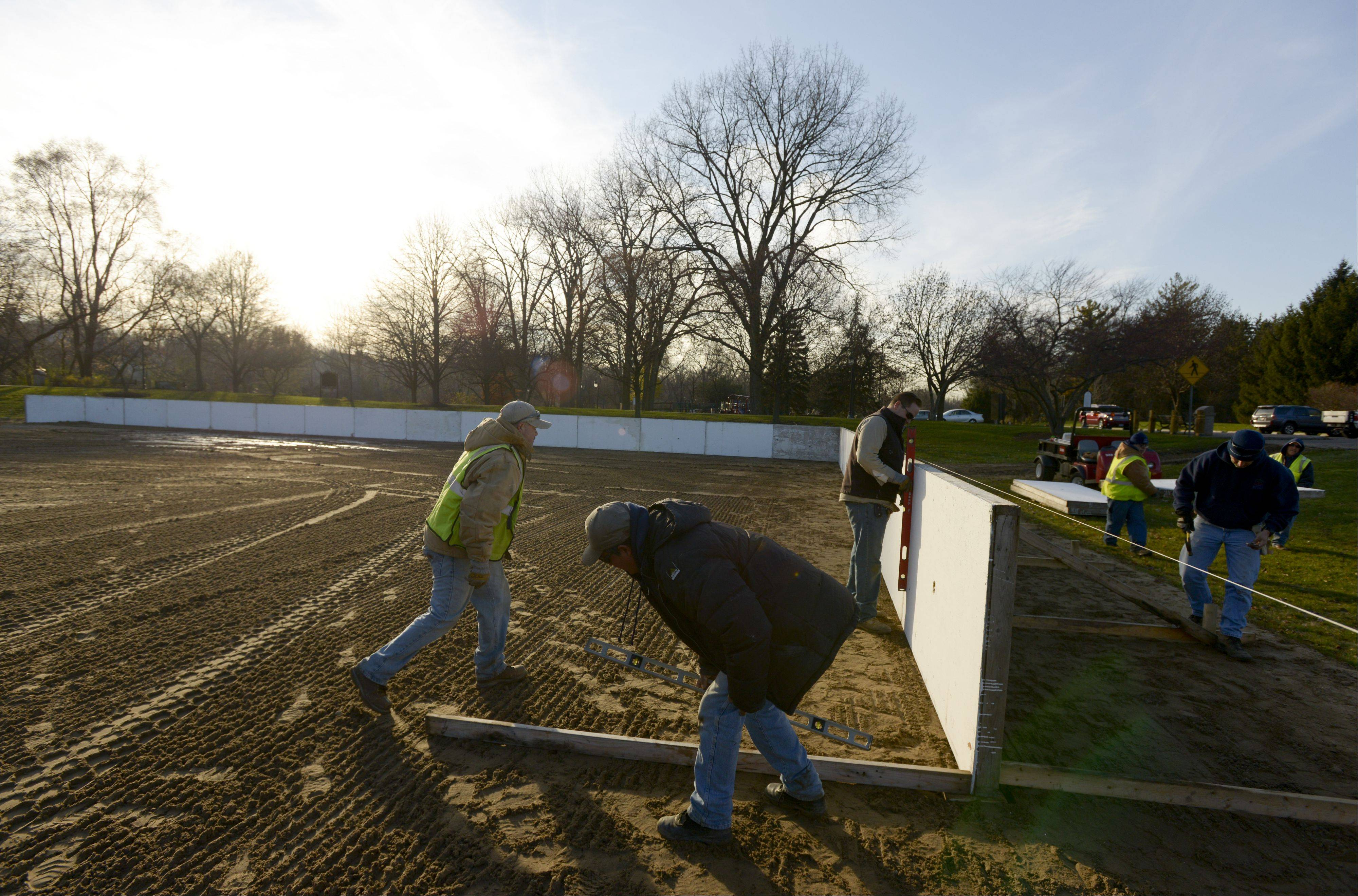 The late afternoon sun shines on Naperville Park District employees as they finish work on the first day of a two- or three-day project to set up ice rinks at Centennial Park.
