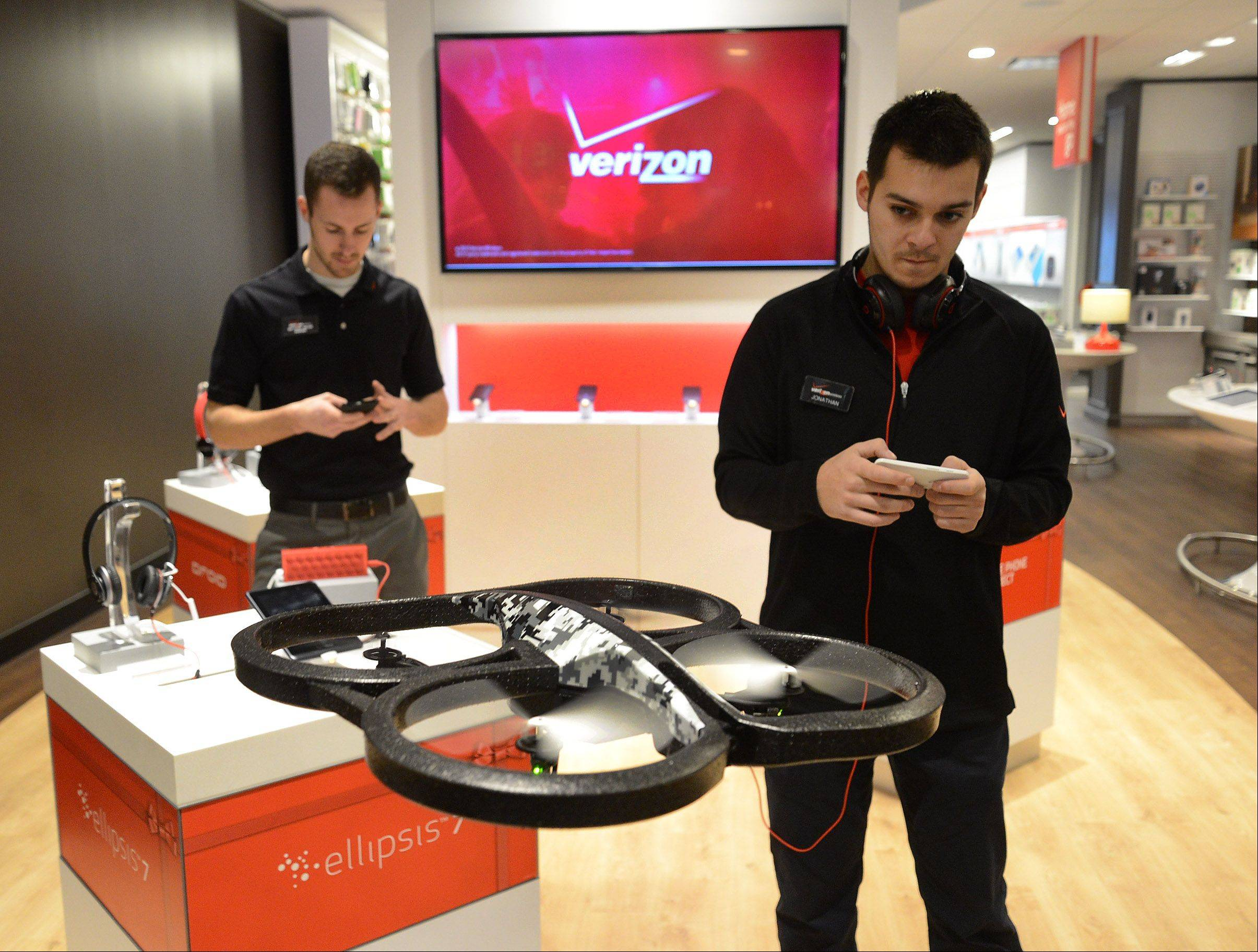 Solution Specialist Jonathan Deassis demonstrates an AR Drone, which records video and takes pictures while controlled by remote control from a cellphone, at Verizon Wireless' new Smart Store in Woodfield Mall.