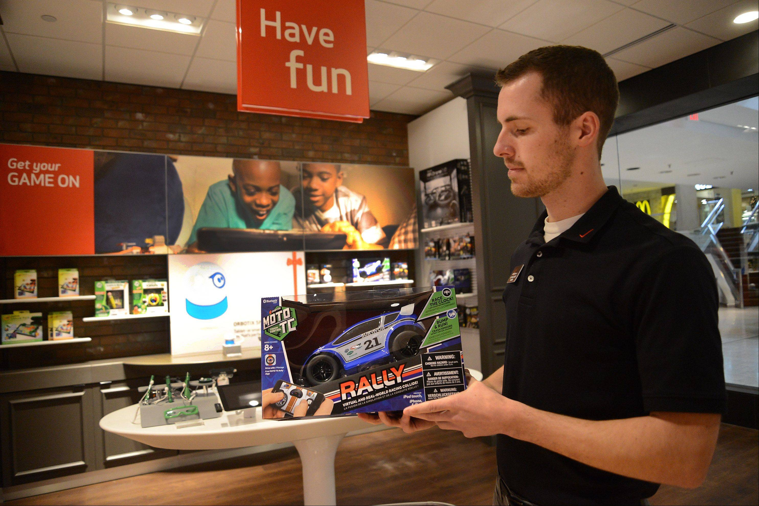 Solutions Manager Nathan Muhr holds a Moto TC Rally Car at the Have Fun Smart Zone inside Verizon Wireless' new Smart Store in Woodfield Mall.