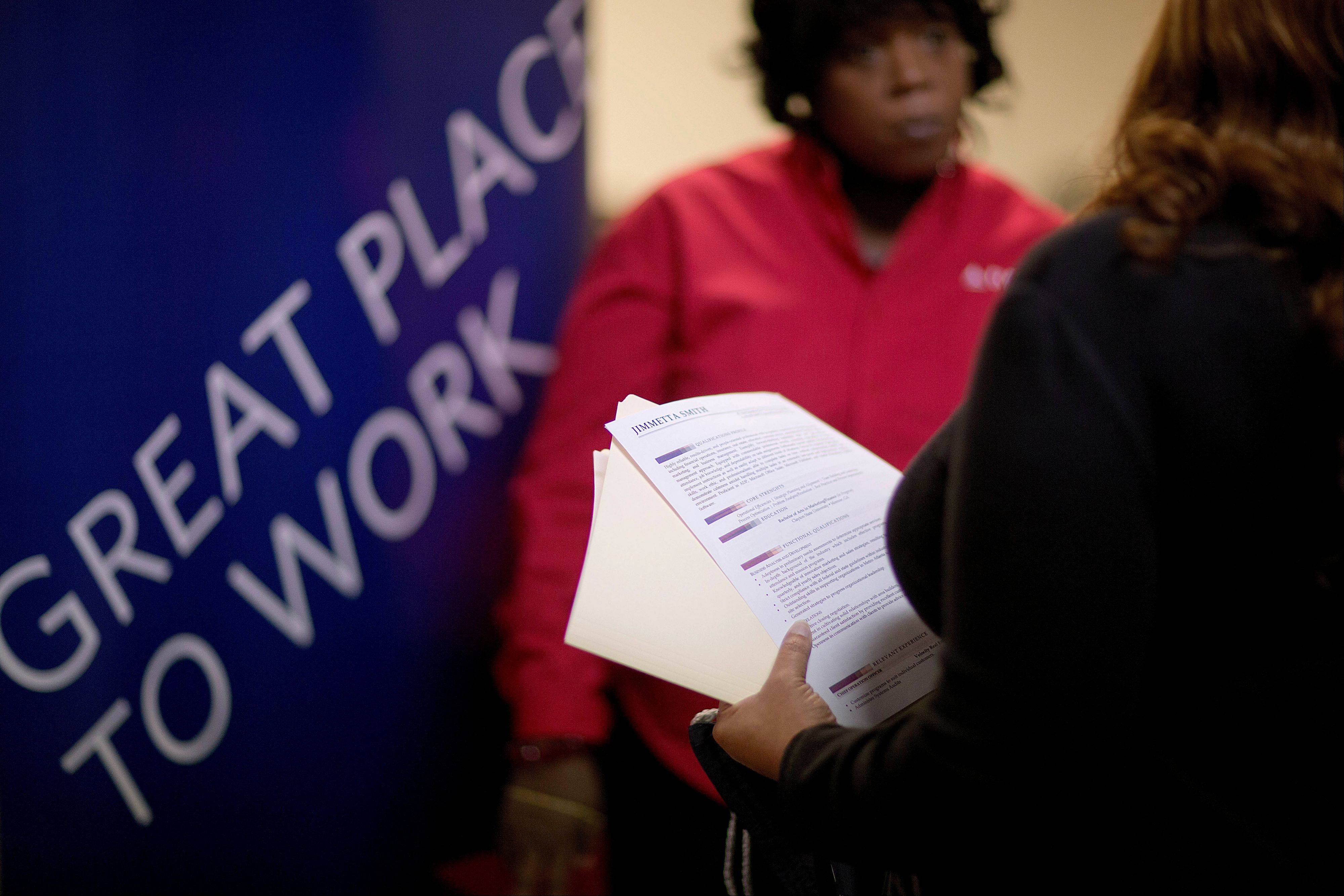 Jimmetta Smith of Lithonia, Ga., right, the wife of a U.S. Marine veteran, holds her resume while talking with Rhonda Knight, a senior recruiter for Delta airlines, at a job fair for veterans and family members at the VFW Post 2681, in Marietta, Ga.