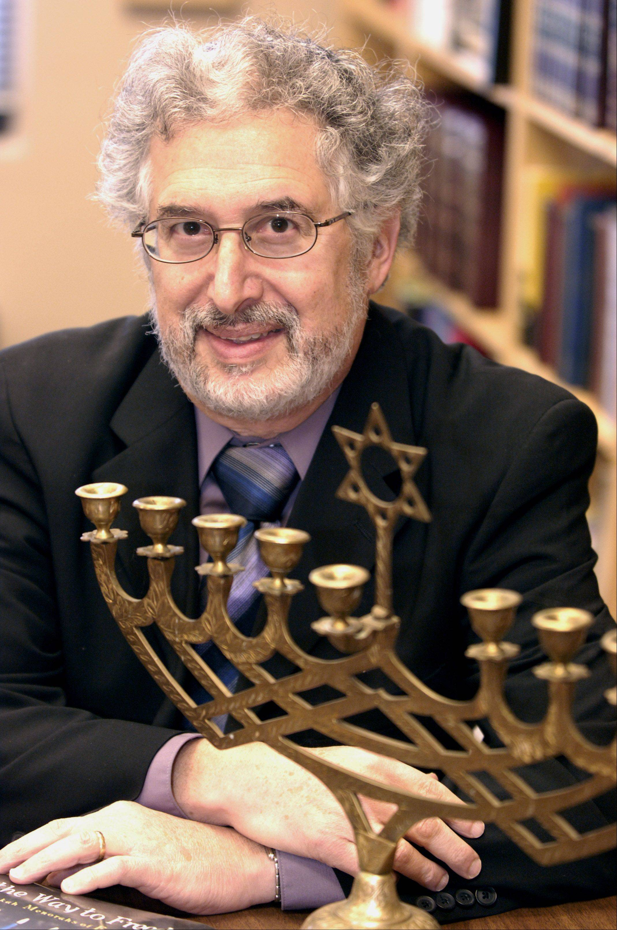 "In this 2011 photo, Rabbi Marc Rudolph of Congregation Beth Shalom in Naperville poses with a traditional Menorah. As Hanukkah coincides with Thanksgiving this year, Rudolph could use a ""Menurkey,"" a turkey-shaped Menorah with candles serving as the tail feathers that's being sold online."