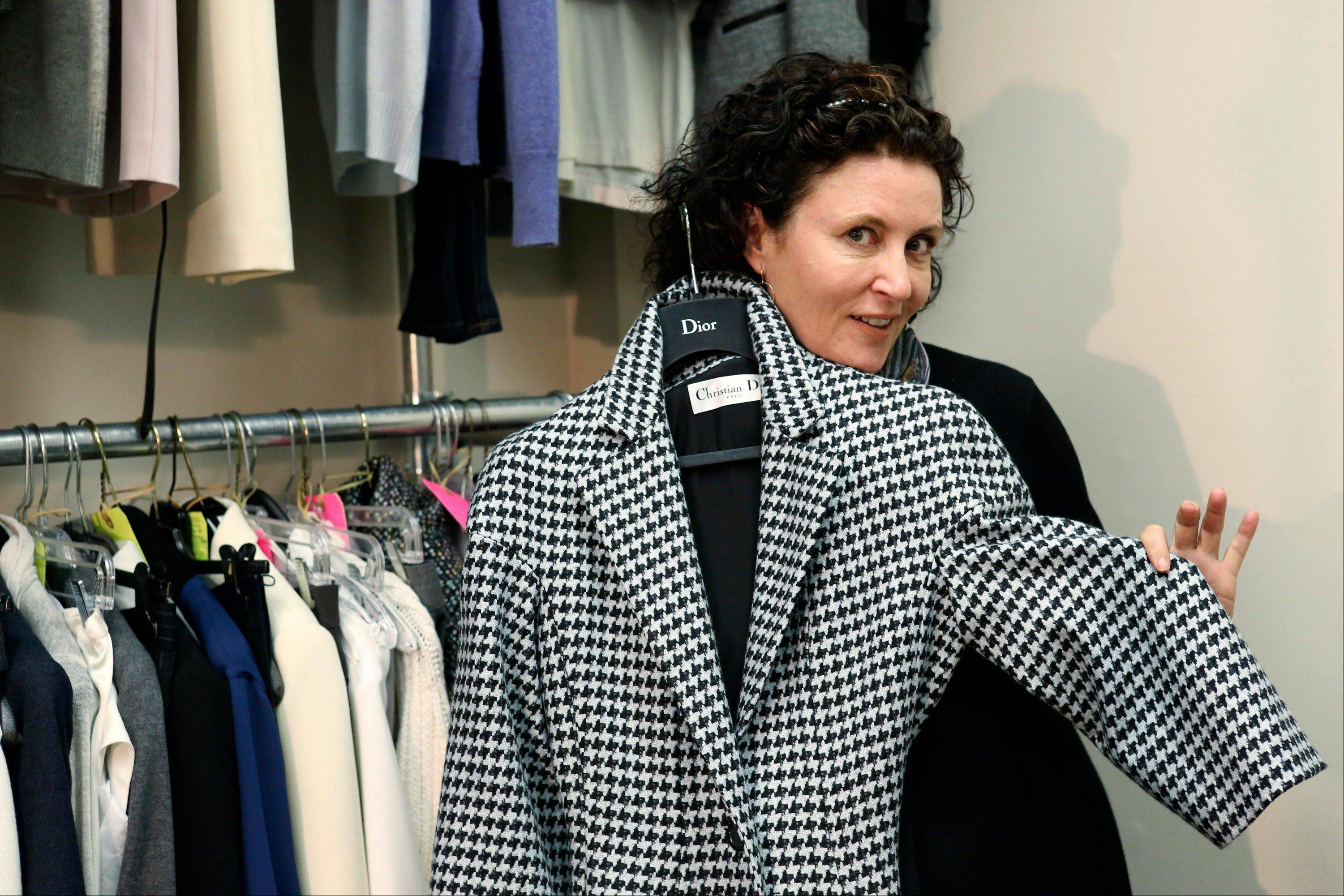 "Costume designer Lyn Paolo holds a Christian Dior coat worn by actress Kerry Washington for the ABC drama series ""Scandal"" in the show's wardrobe closet on the Sunset Gower lot in Los Angeles."