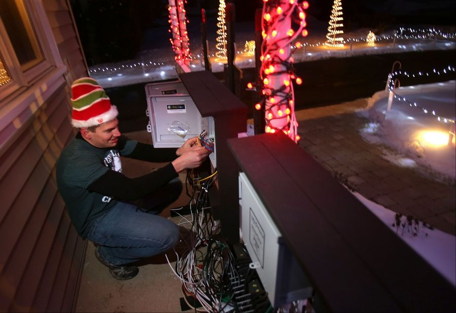 Mark Tarkowski works on a connection box that controls his lighting outside his home at 653 Walnut Road in Wauconda.