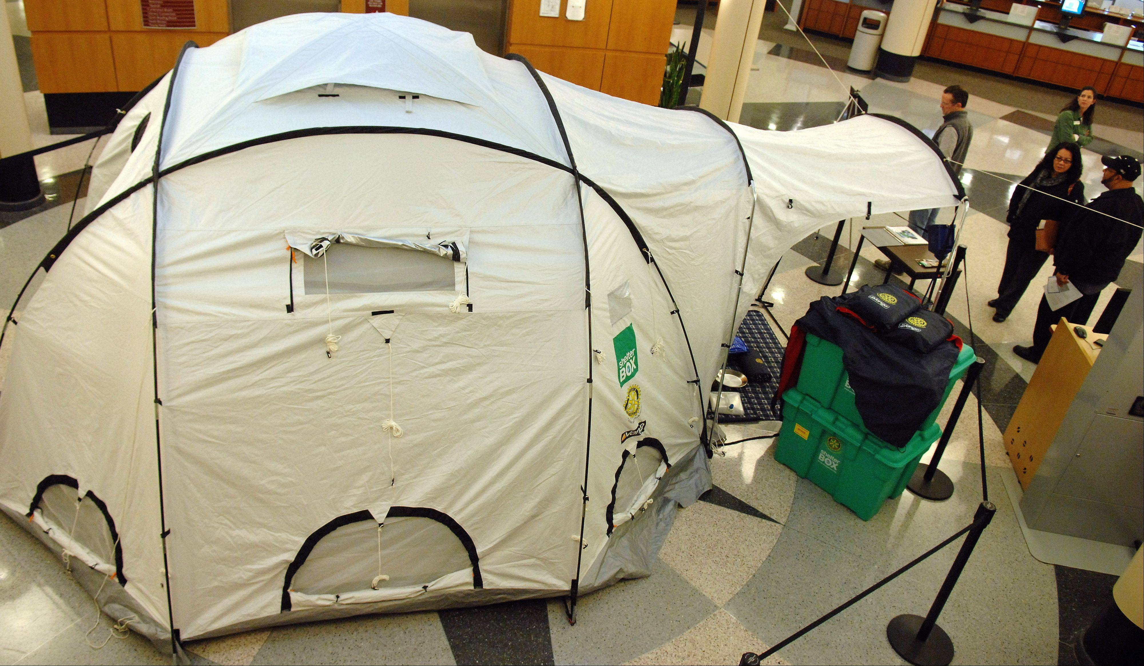 Library goers check out a Shelter Box which includes a 10-person tent & Gail Borden Library showcases Shelter Box survival kit