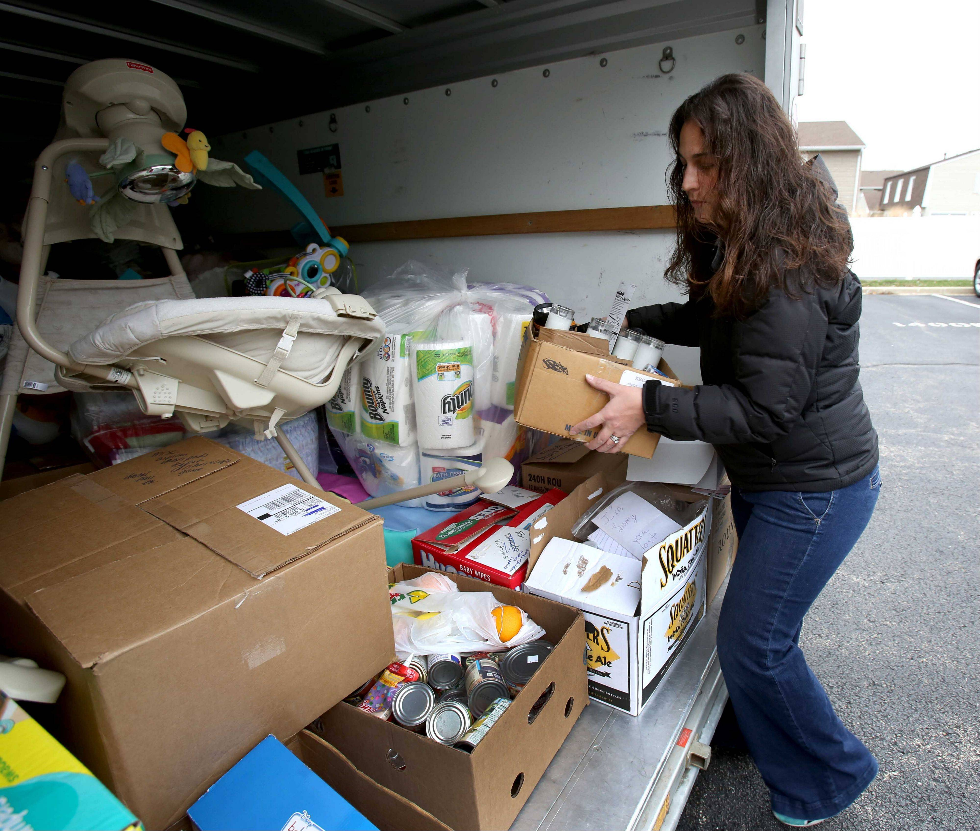 Jennifer Guevara loads up a trailer loaded with donations from a Wheaton parents' Facebook site for tornado victims in Coal City.