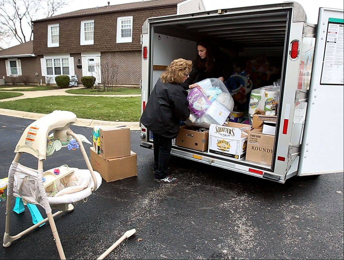 Terry Jessen of Lombard helps her daughter Jennifer Guevara load a trailer Thursday with donated items for the victims of the tornado in Coal City. She gathered donations after she posted on a Facebook she manages.