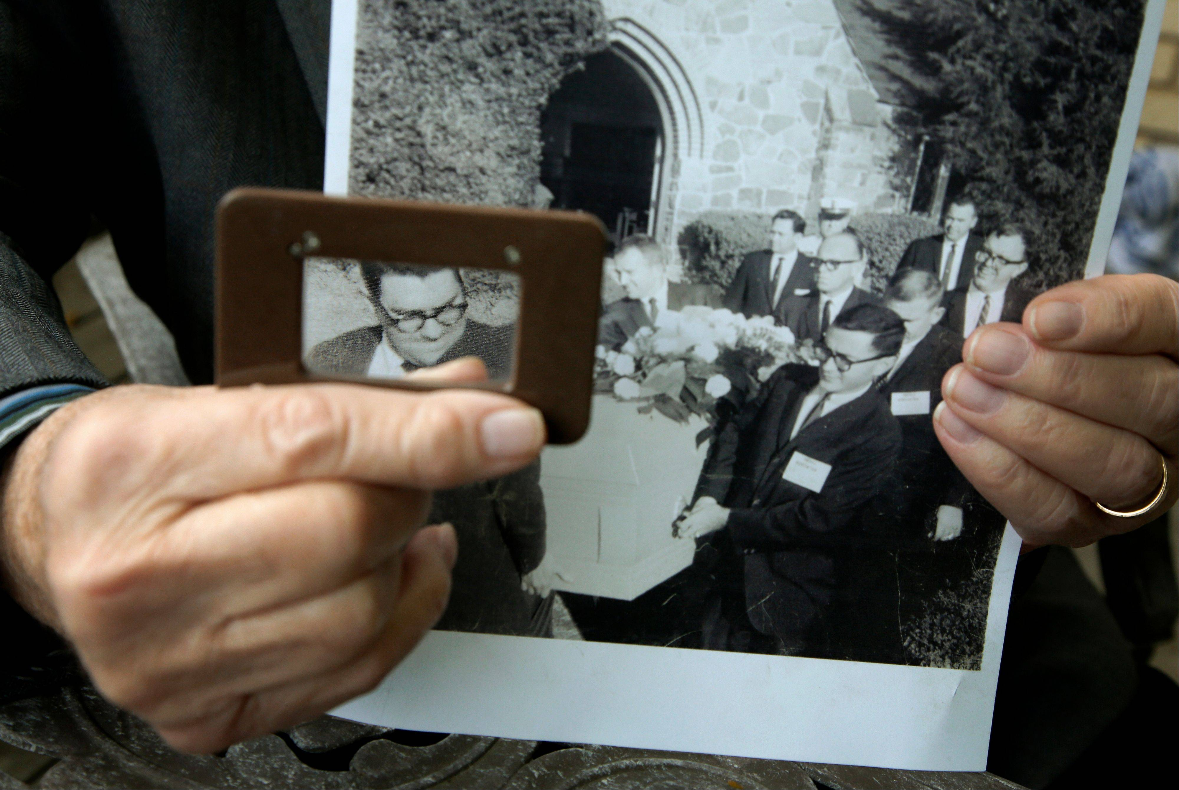 Former AP writer Mike Cochran uses a magnifying glass to highlight his face along with other reporters serving as pallbearers for Lee Harvey Oswald.