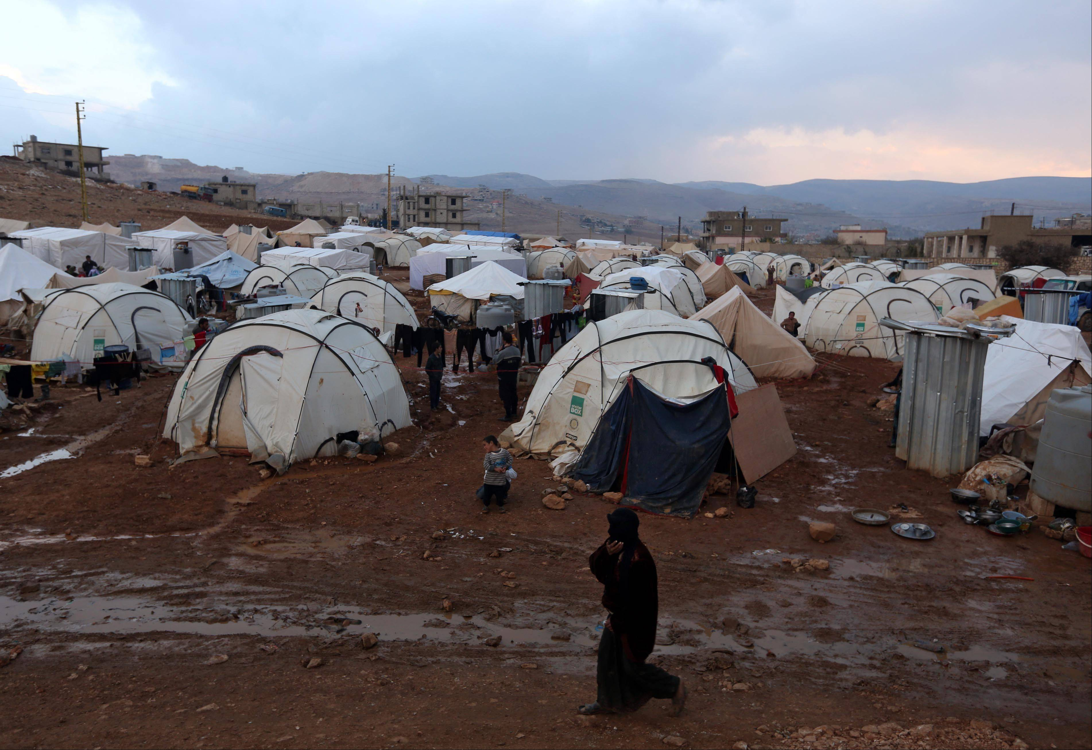 A Syrian refugee woman walks Monday near the tents of a refugee camp in the eastern Lebanese border town of Arsal. Thousands of Syrians have fled to Lebanon over the past days as government forces attack the western town of Qarah near the border with Lebanon.