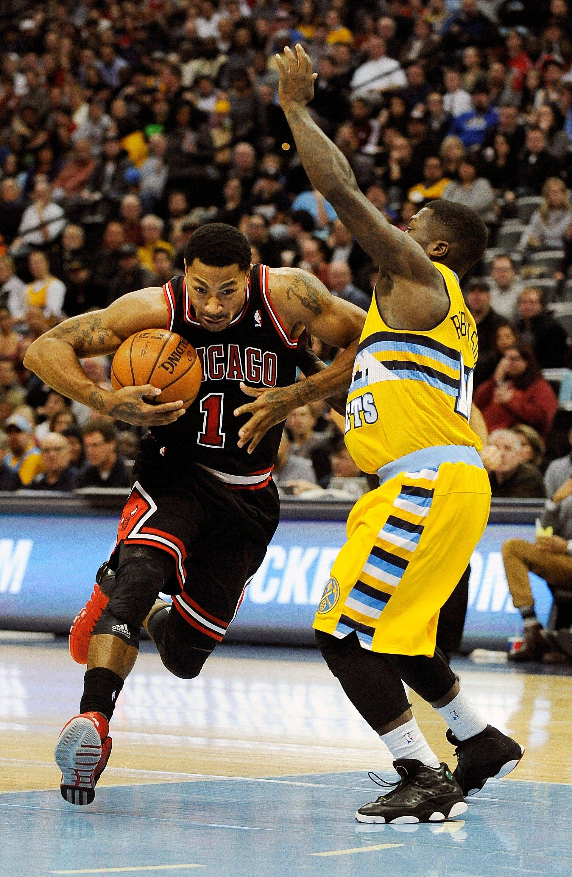 Chicago Bulls point guard Derrick Rose, left, drives against Denver Nuggets point guard Nate Robinson, right, in the first quarter of an NBA basketball game on Thursday, Nov. 21, 2013, in Denver.