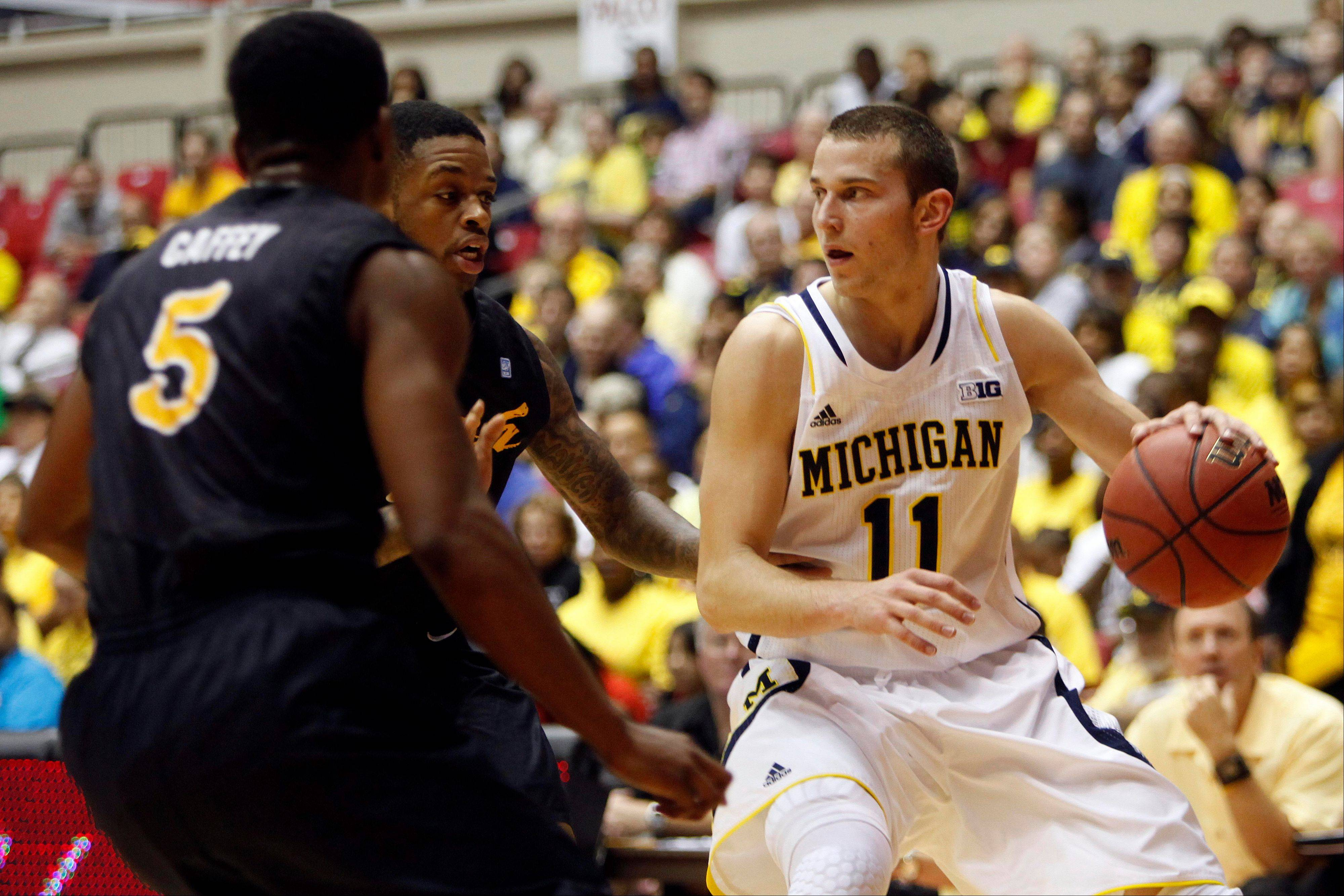 Long Beach State's Mike Caffey, left, and Kris Gulley pressure Michigan's Nik Stauskas in Thursday's game in San Juan, Puerto Rico.
