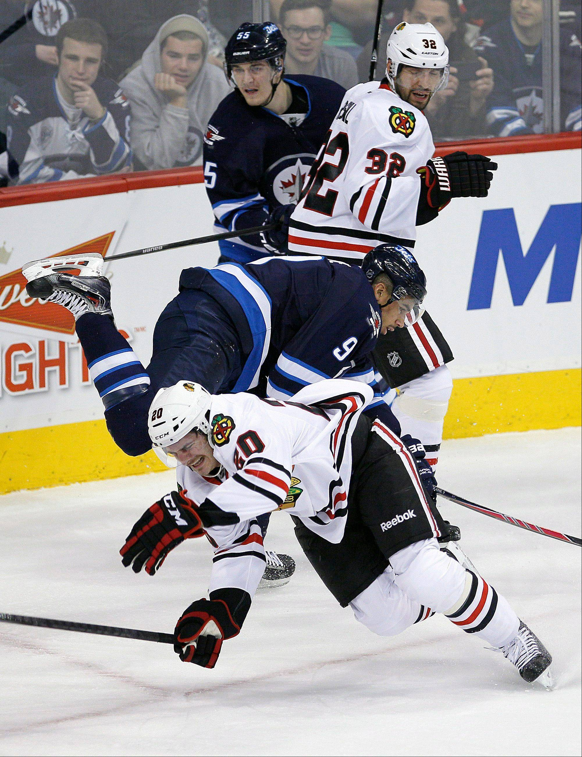 Winnipeg's Evander Kane and Brandon Saad collide as the Jets' Mark Scheifele, back, and the Blackhawks' Michal Rozsival stand by during the first period in Winnipeg, Manitoba on Thursday.