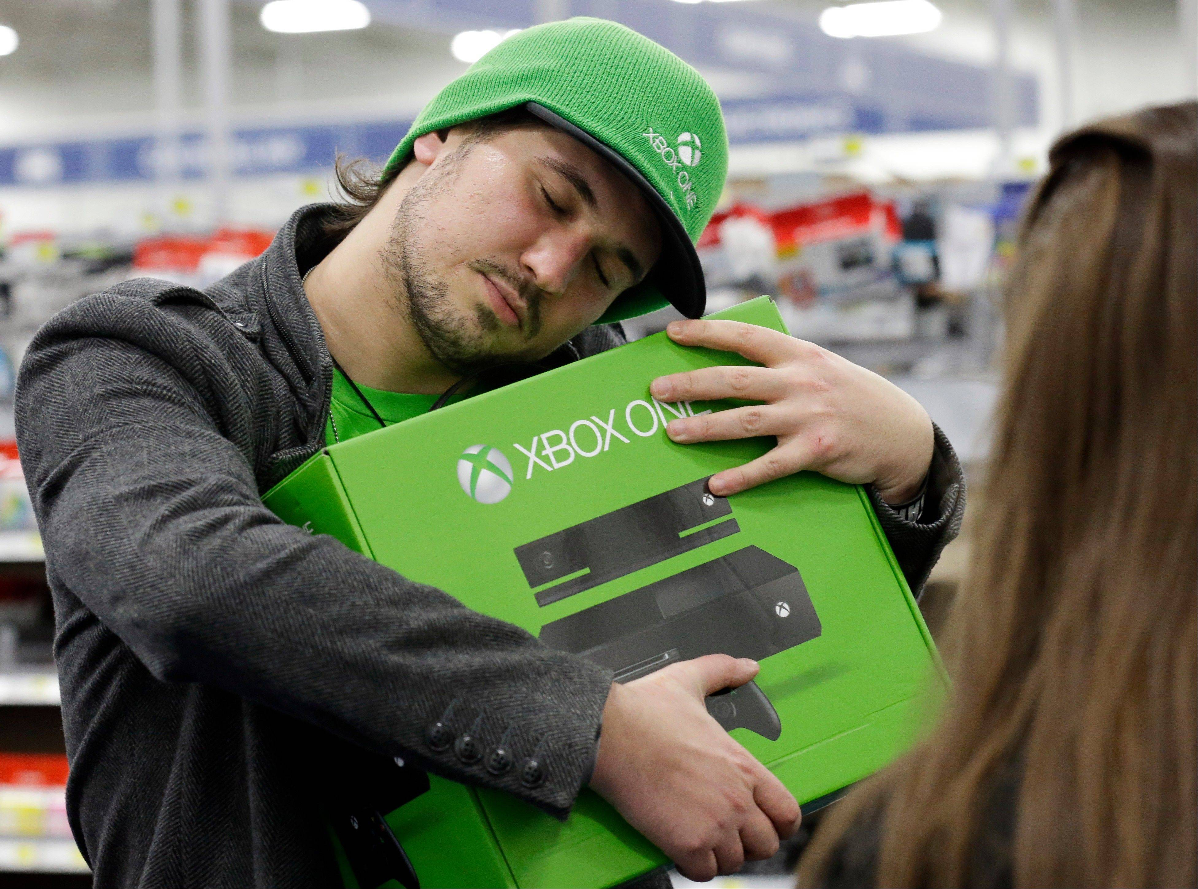 Associated Press Emanuel Jumatate, from Chicago, hugs his new Xbox One at a Best Buy on Friday, Nov. 22, 2013, in Evanston. Microsoft is billing the Xbox One, which includes an updated Kinect motion sensor, as an all-in-one entertainment system rather than just a gaming console.