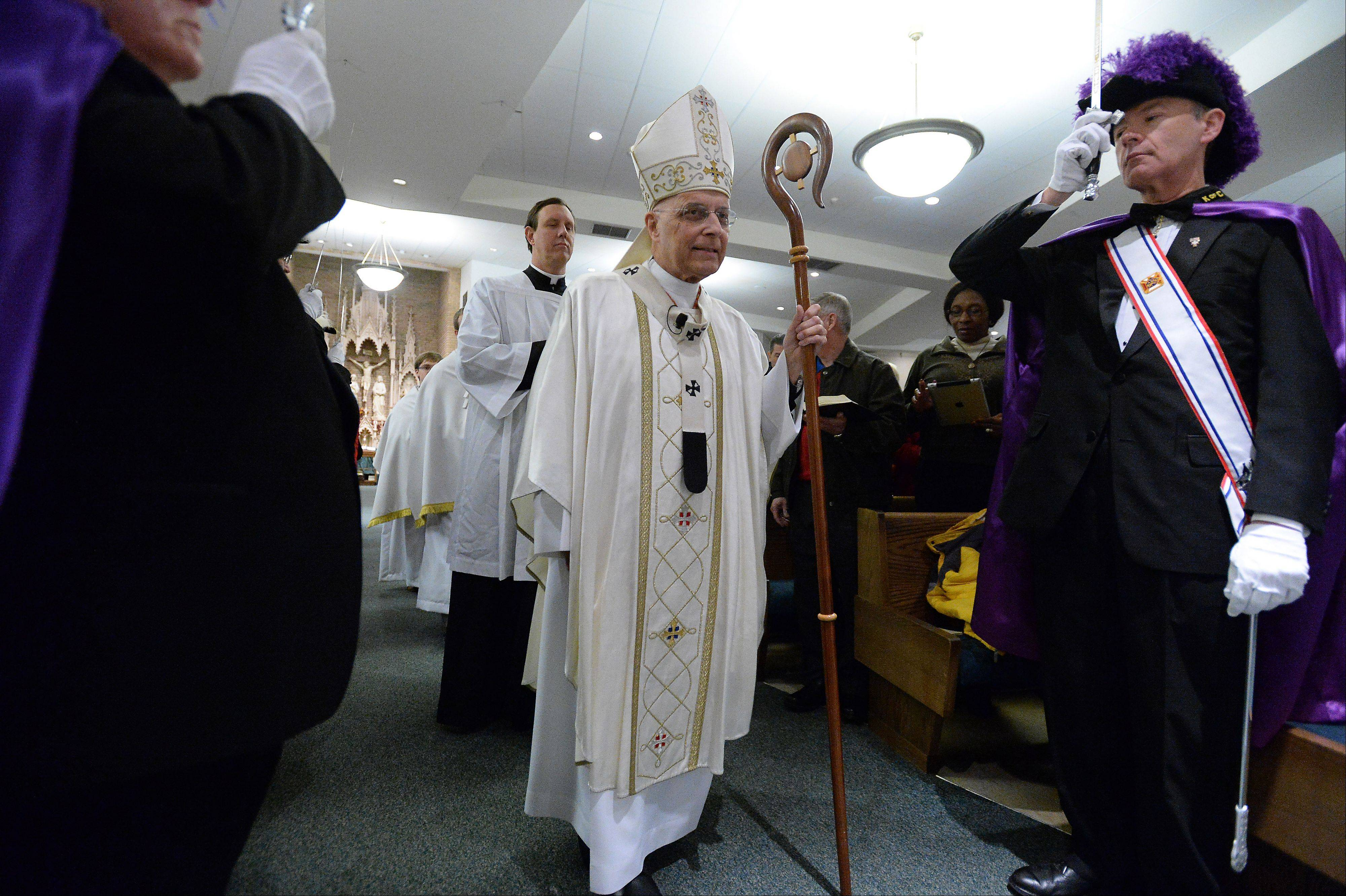 "Cardinal George leads the procession into St. Mary's Church with the Knights of Columbus to celebrate Mass Saturday as part of ""Day of Catholic Education"" in Buffalo Grove."