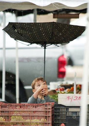 Jacob Melville, 4, of Irvine, Calif., catches rain drops as he holds the umbrella for his mother, Brandie, at the farmer's market in Laguna Hills, Calif., on Friday, Nov. 22, 2013. Rain throughout the West led to flooding Friday in parts of California.