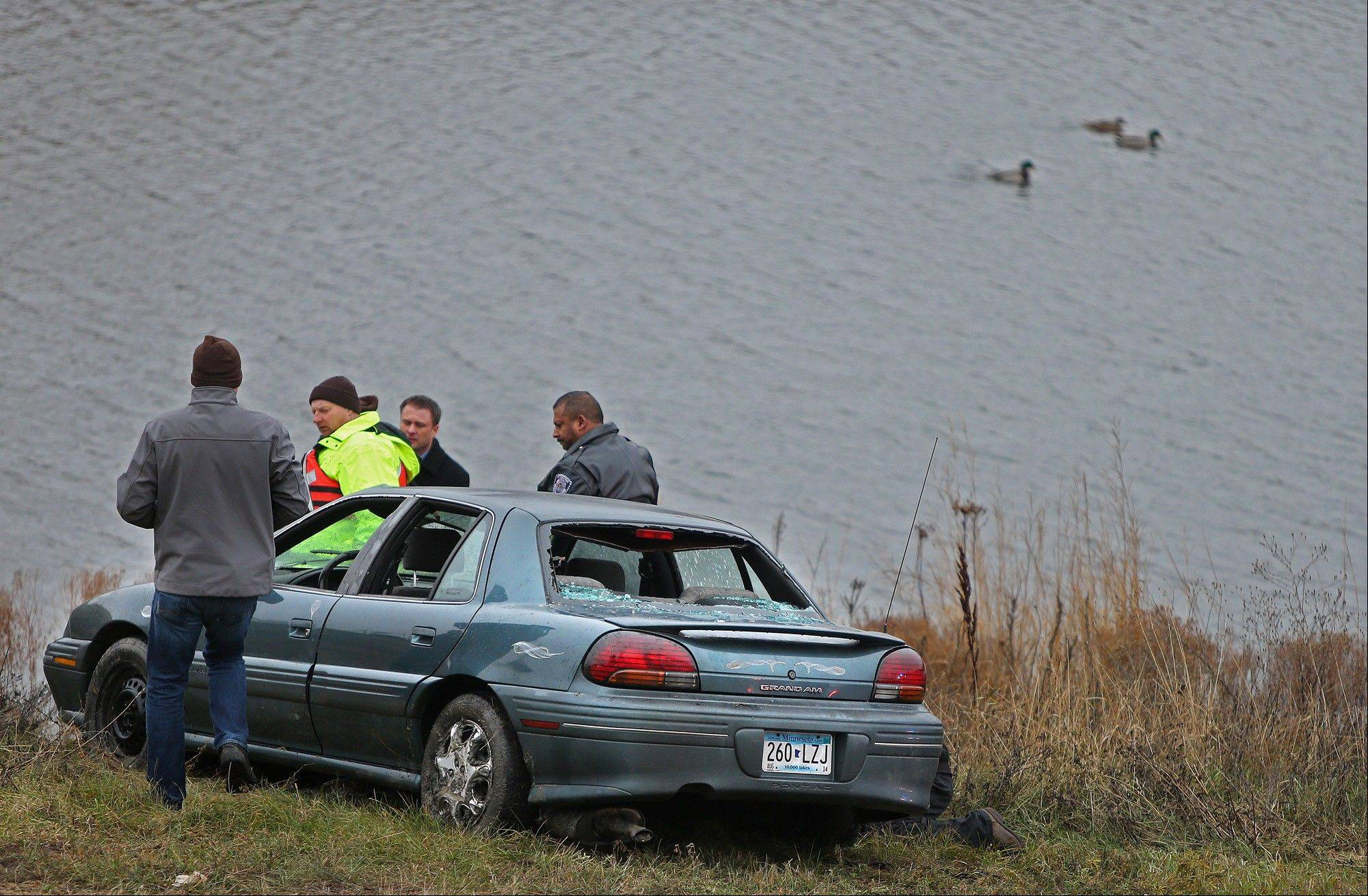 Investigators look at a car Thursday that veered off a suburban Minneapolis highway ramp and plunged into a storm water pond with five children, ages 1 to 7, aboard.