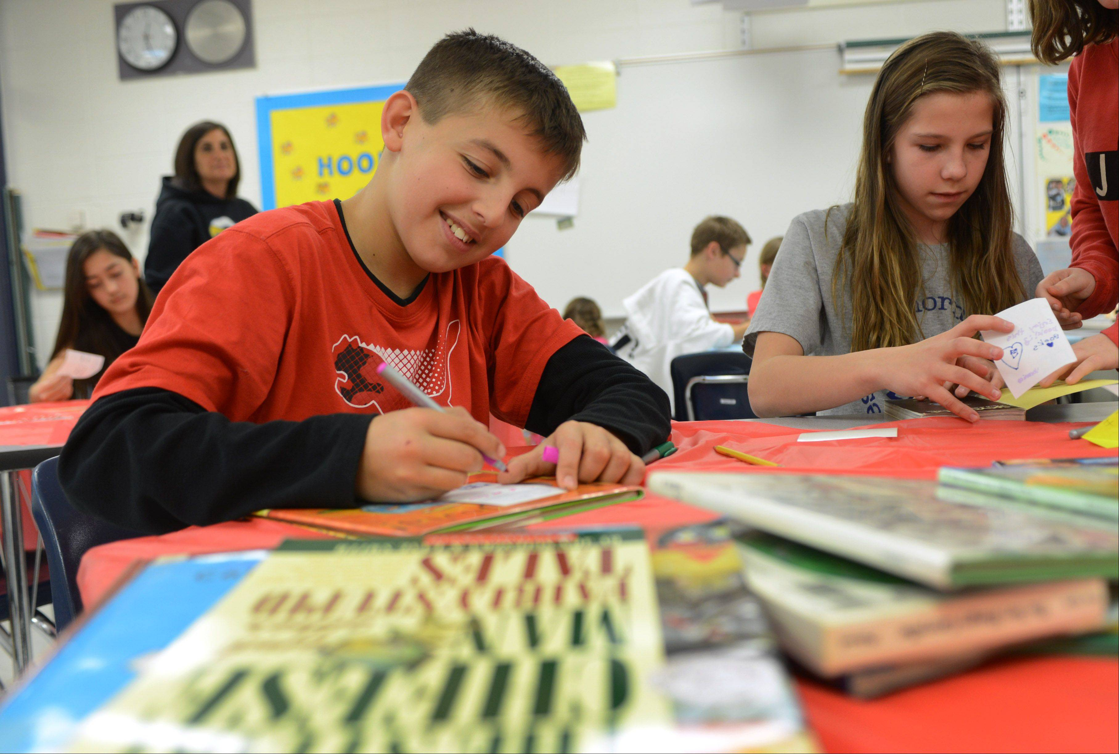 Hawthorn Middle School North sixth grade students Michael Svistun, left, and Veronica Gawin write personal notes to place inside donated books at the Vernon Hills school Friday. Students in Rachel Serlin's Language Arts classes collected around 500 books to donate to PADS Lake County.