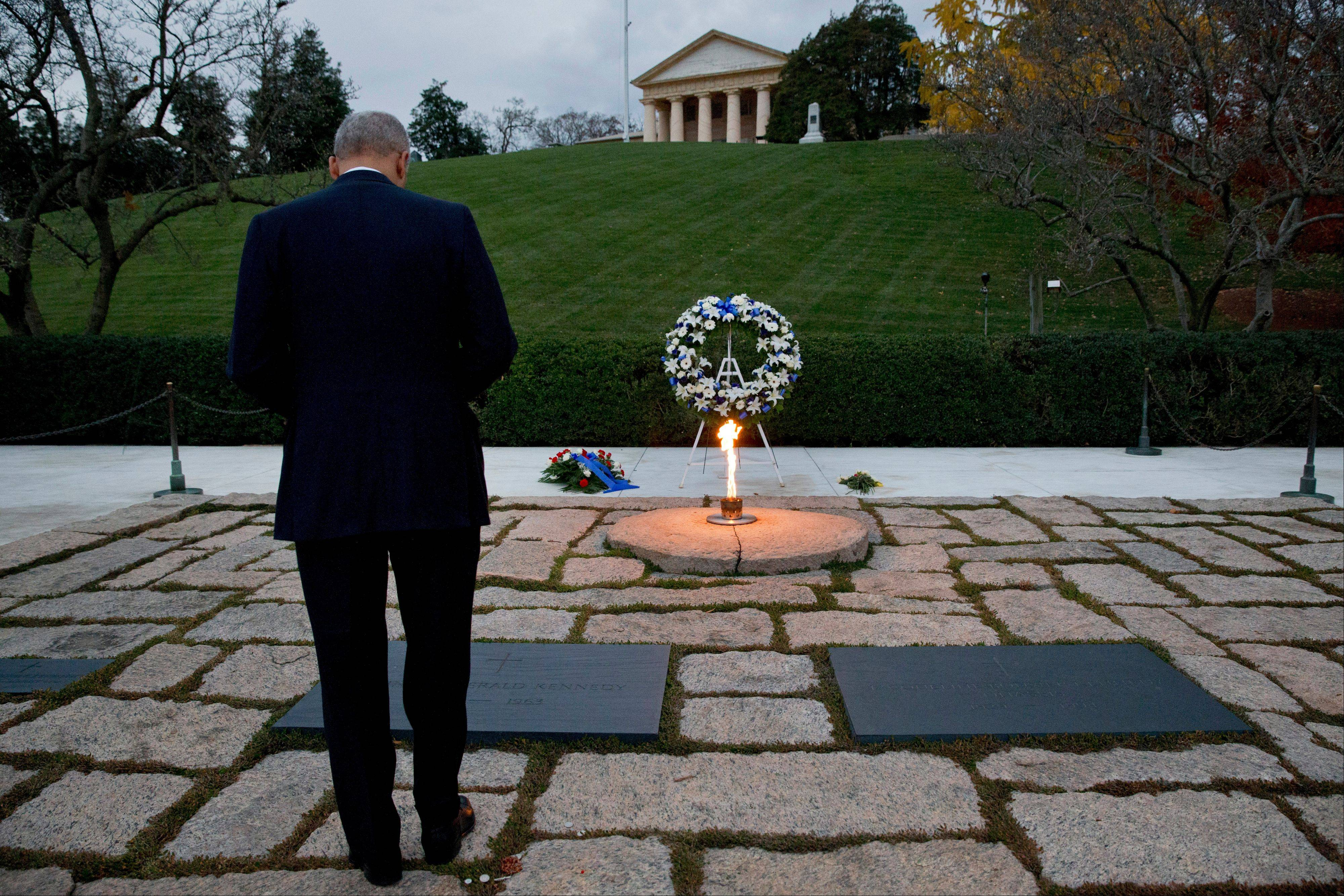 Attorney General Eric Holder pays his respects at the grave of John F. Kennedy at Arlington National Cemetery on Friday, Nov. 22, 2013, on the 50th anniversary of Kennedy's death. Holder has been visiting the grave since his youth.
