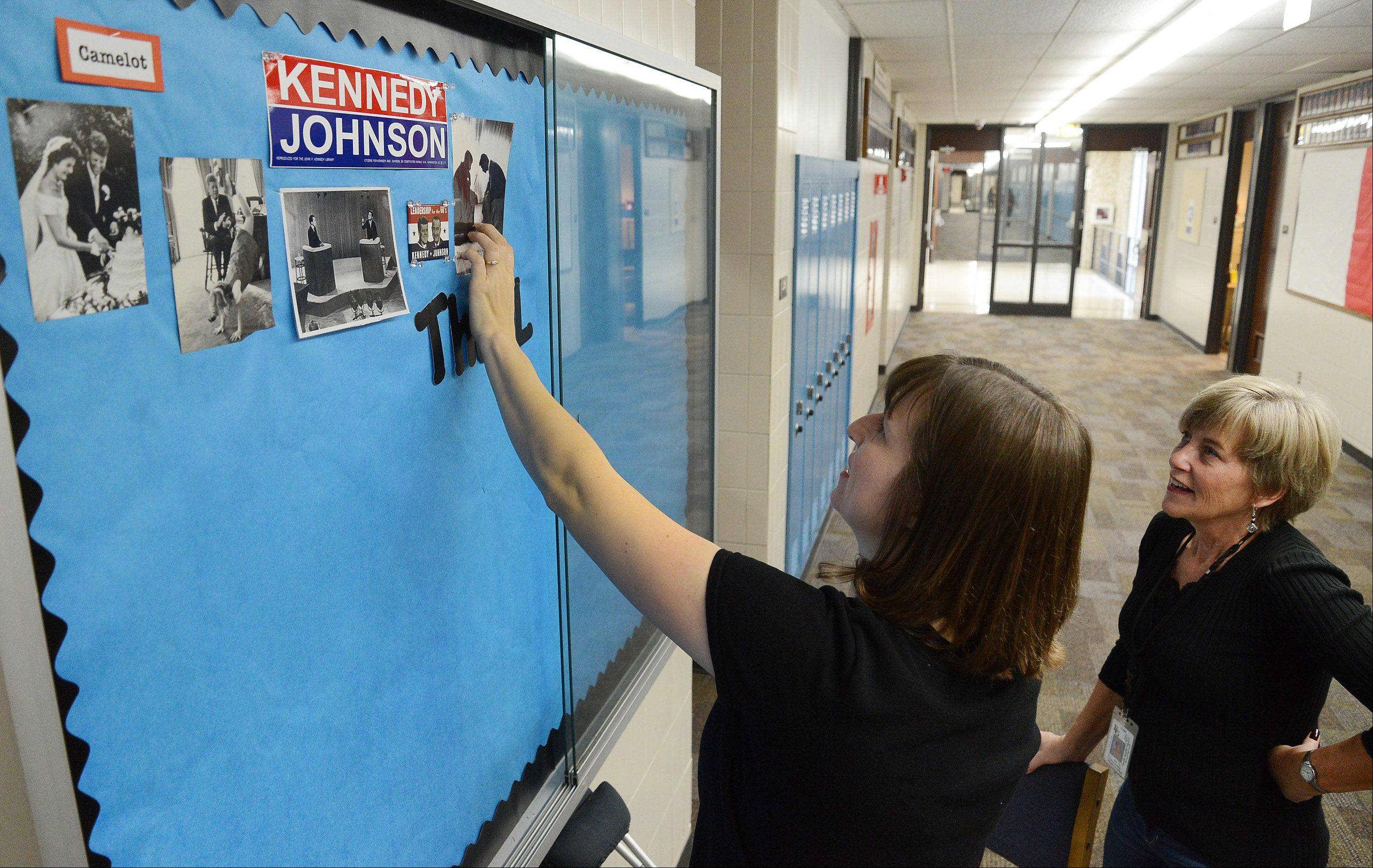 U.S. history teacher Mindy Perkins, left, and Resource Assistant Sue Montemayor work on a display of JFK's legacy at Elk Grove High School.