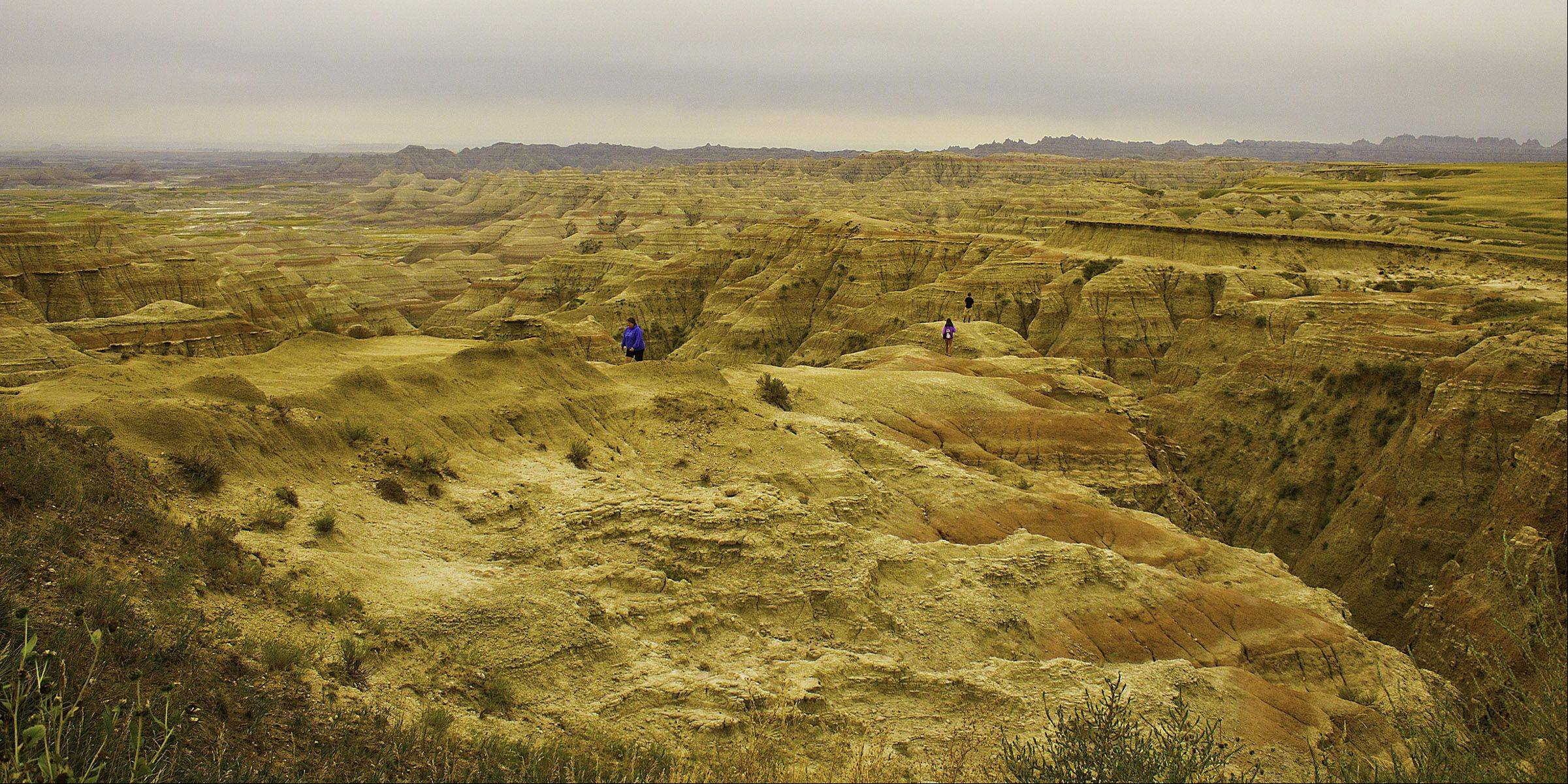 Hikers climb the cliffs in the South Dakota Badlands on September 8th looking at its immense size, colorations and unique beauty.