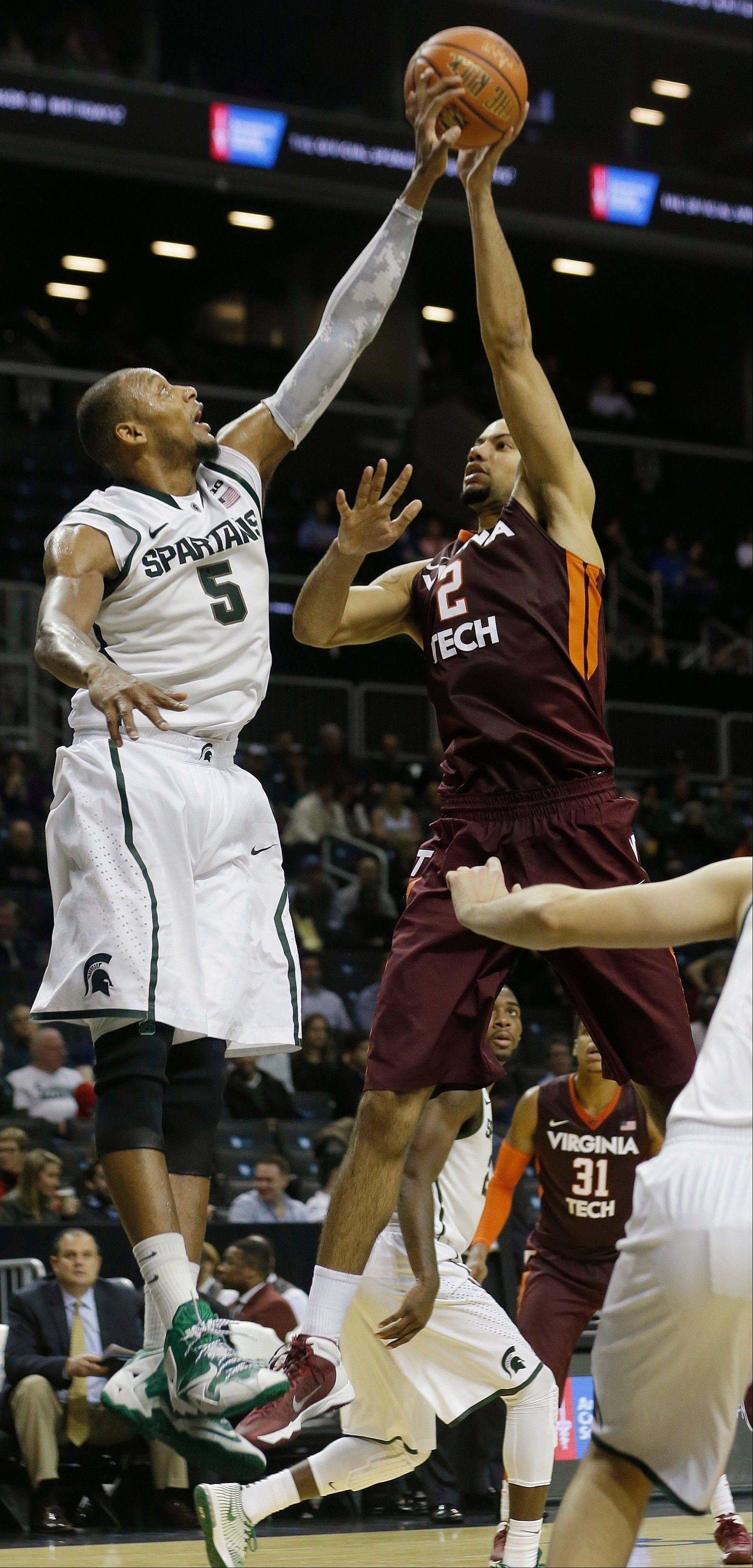Michigan State�s Adreian Payne blocks a shot by Virginia Tech�s Joey Van Zegeren during the second half of a Coaches vs. Cancer Classic game on Friday in New York.