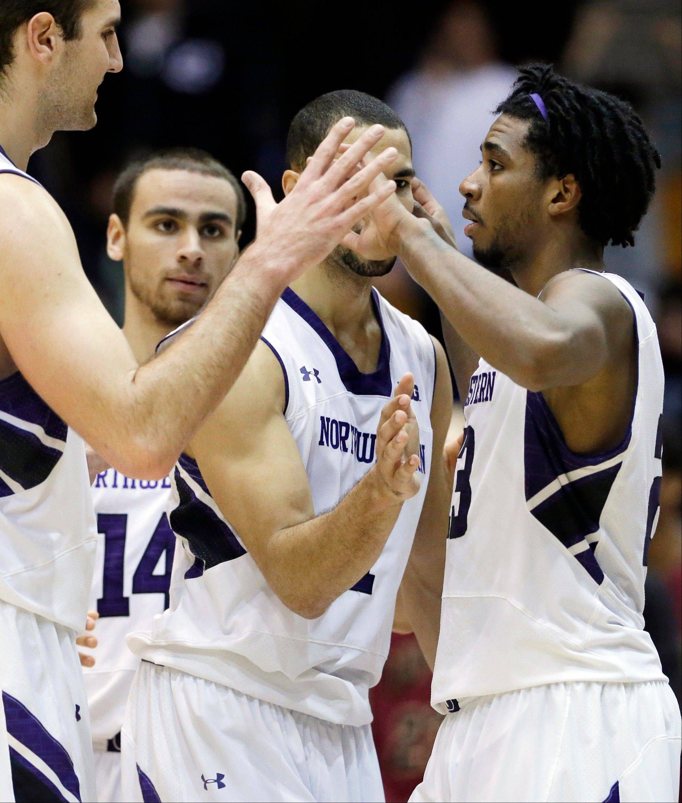 Northwestern guard JerShon Cobb, right, celebrates with teammates after Northwestern defeated IUPUI 63-61 on Friday in Evanston.