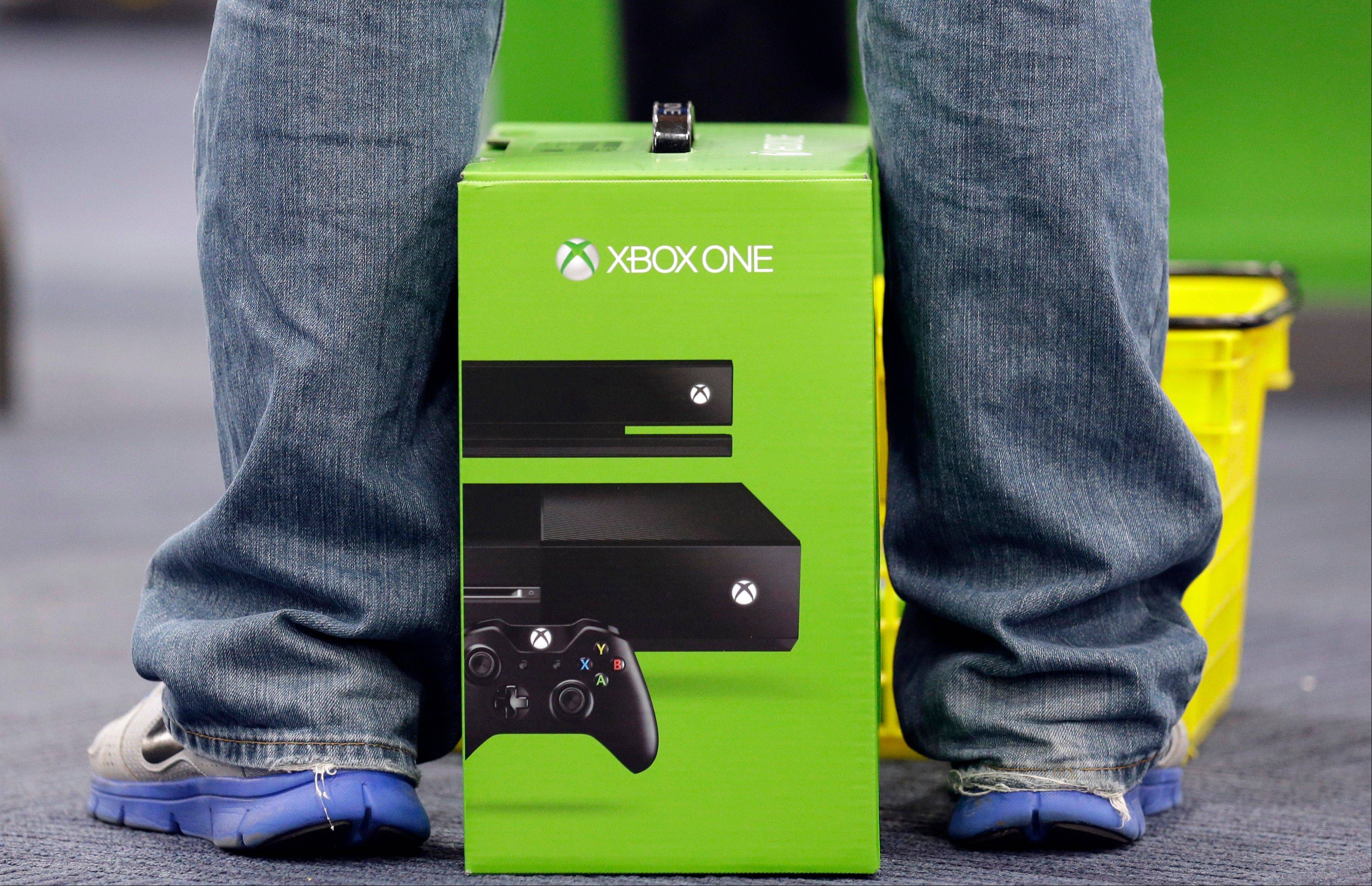 A man puts his newest XBox One on the floor Friday after he purchased it at a Best Buy in Evanston. The Xbox One, which includes an updated Kinect motion sensor, cost $500. Microsoft is billing it as an all-in-one entertainment system rather than just a gaming console.