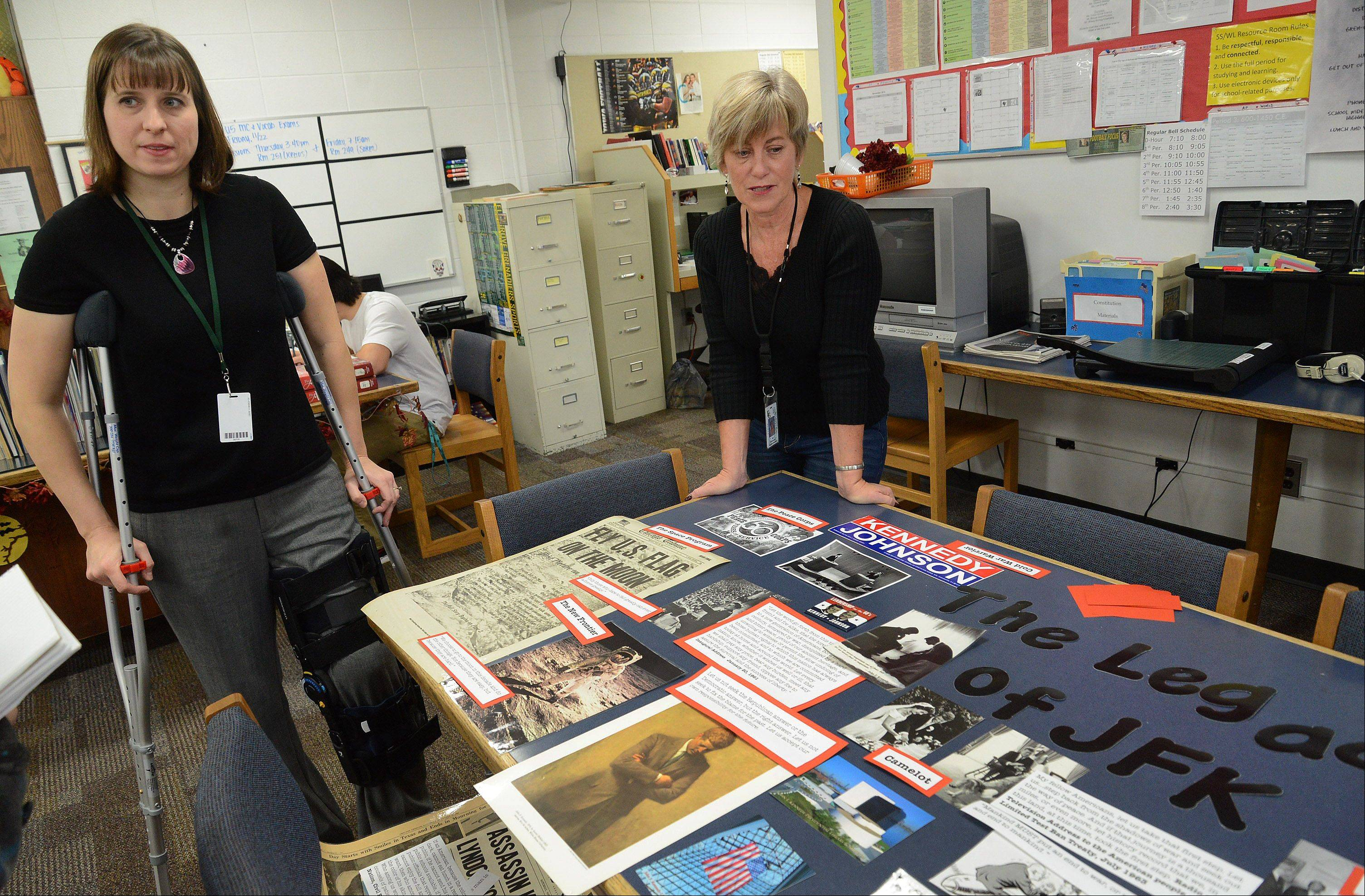 Teacher Mindy Perkins, left, and Resource Assistant Sue Montemayor pull together a display on the legacy of JFK.