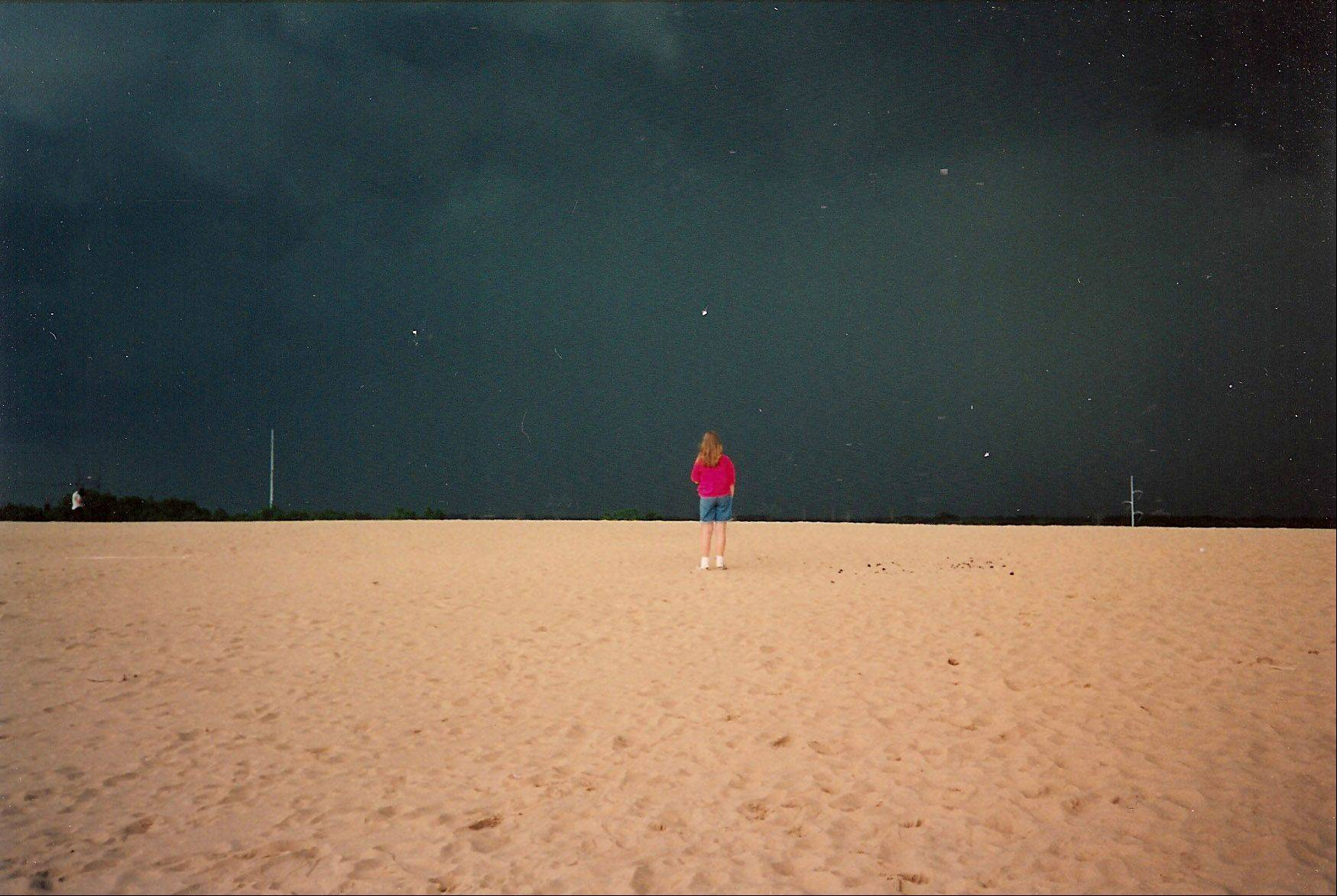 A girl stands on the Mt. Baldy sand dune in the Indiana Dunes State Park on August of 1995. A huge storm was coming from the northwest but the sun still shone brightly in the southeast, hence the very dark sky and everything else in the foreground brightly lit.