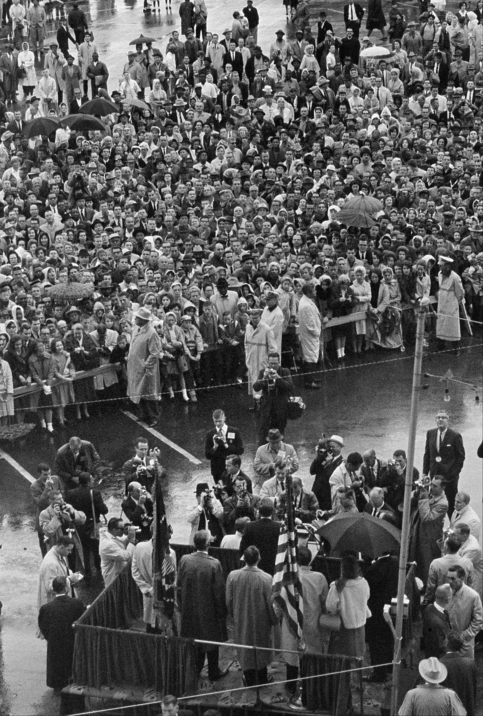 "In this Nov. 22, 1963 file photo, President John F. Kennedy, center on foreground platform, addresses a rain-soaked crowd in Fort Worth, Texas. In an interview, Secret Service agent Clint Hill recalled, ""I heard t"