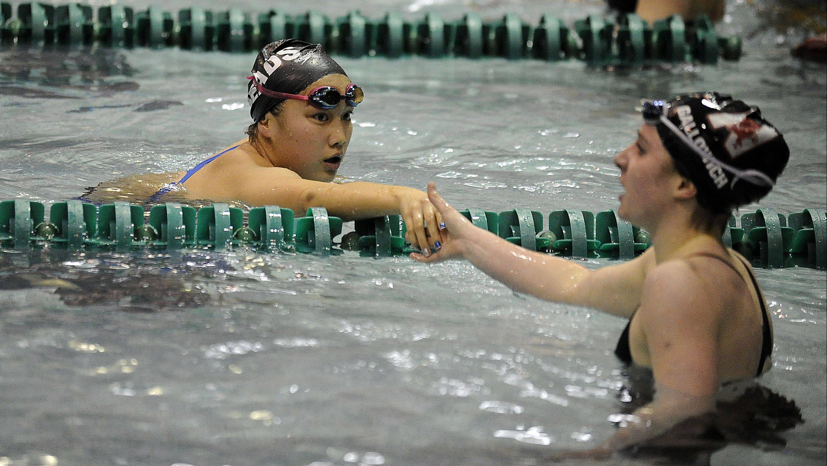 Annie Gosselin of Rosary, left, shakes hands with Kamryn Gallowich of Naperville Central after the 200-yard IM at the girls state finals prelims at New Trier High School on Friday.