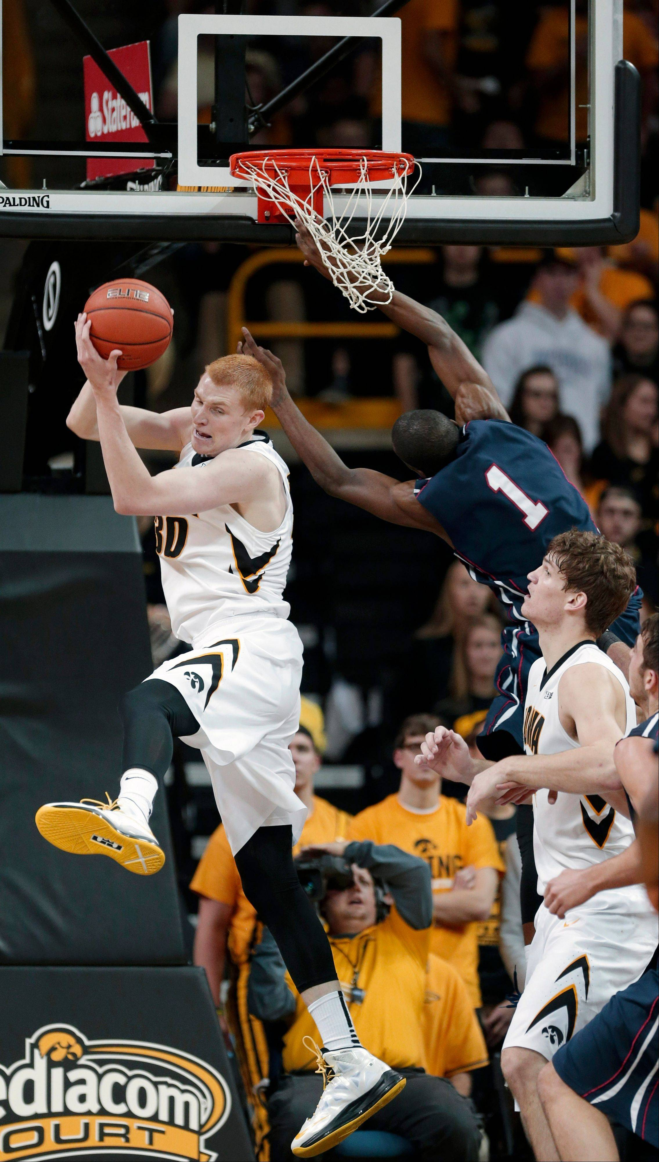 Iowa forward Aaron White, left, grabs a rebound over teammate Adam Woodbury, right, and Penn guard Tony Hicks during the second half of Friday's game in Iowa City.