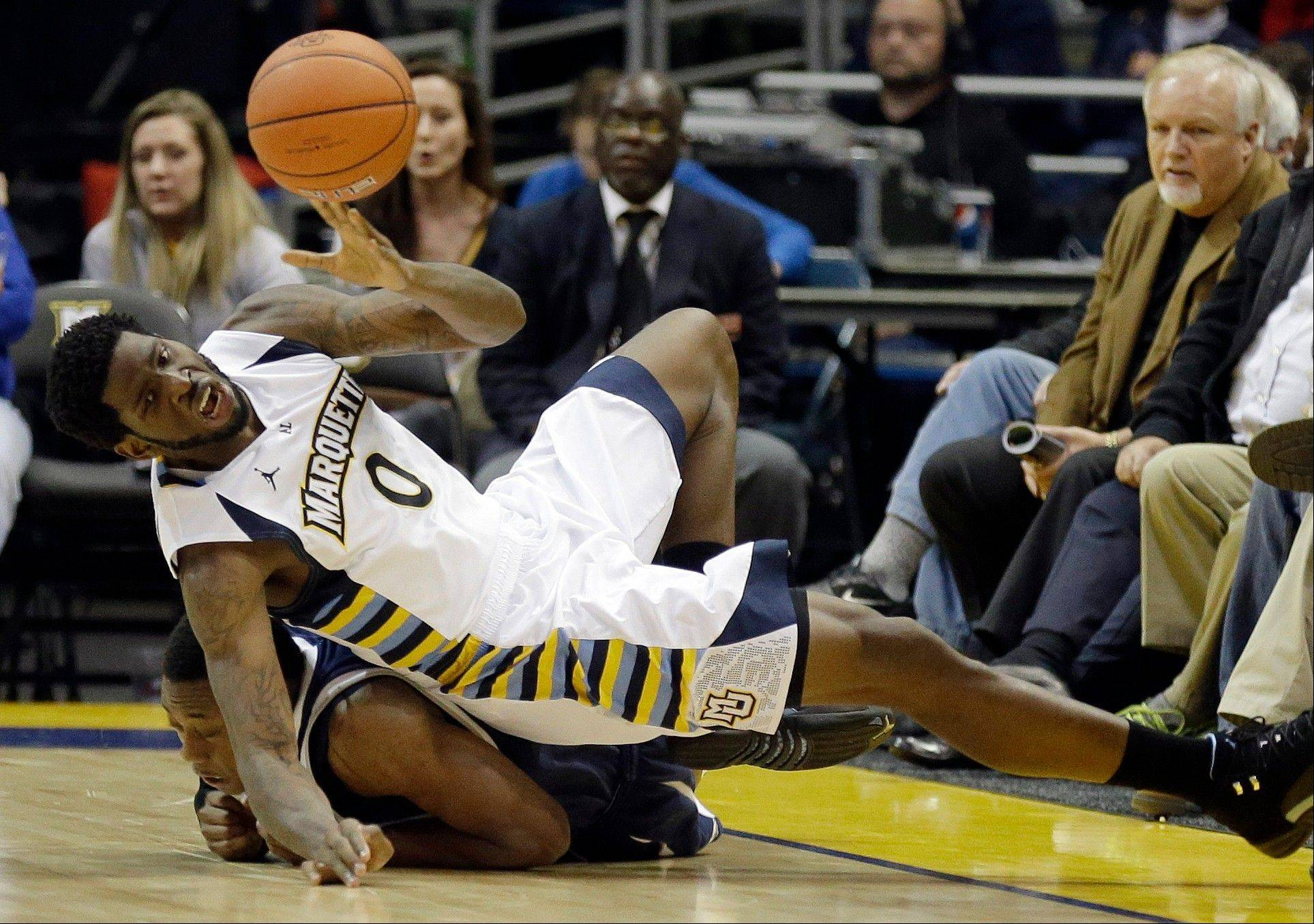 Marquette's Jamil Wilson dives over New Hampshire's Jacoby Armstrong for a loose ball during the second half of Thursday's game in Milwaukee.