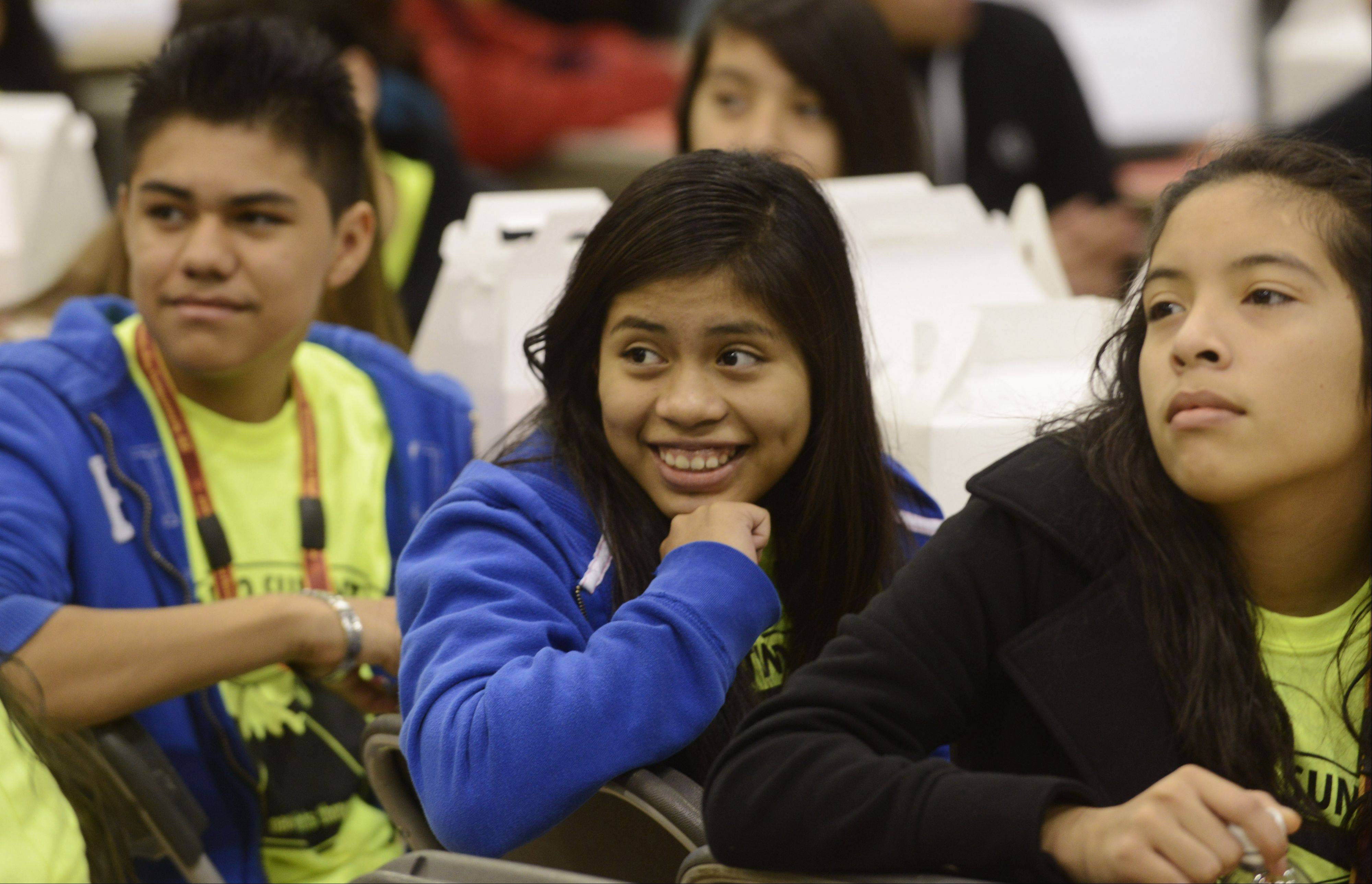 JOE LEWNARD/jlewnard@dailyherald.comSchaumburg High School freshman Anayeli Vazquez, middle, smiles while watching a performance during Friday's Latino Summit at Harper College in Palatine.
