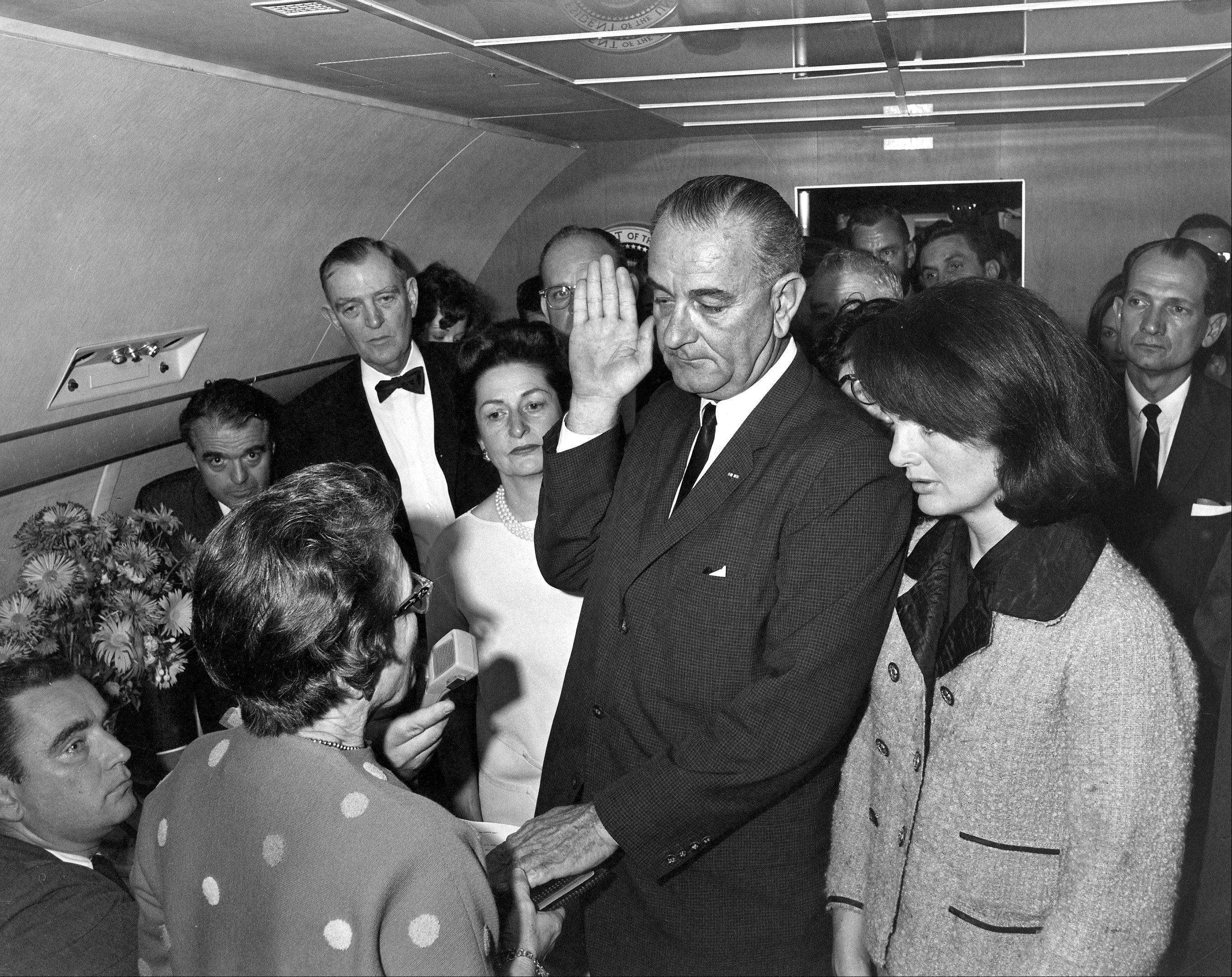 Lyndon B. Johnson is sworn in as president as Jacqueline Kennedy stands at his side in the cabin of the presidential plane on the ground at Love Field in Dallas.