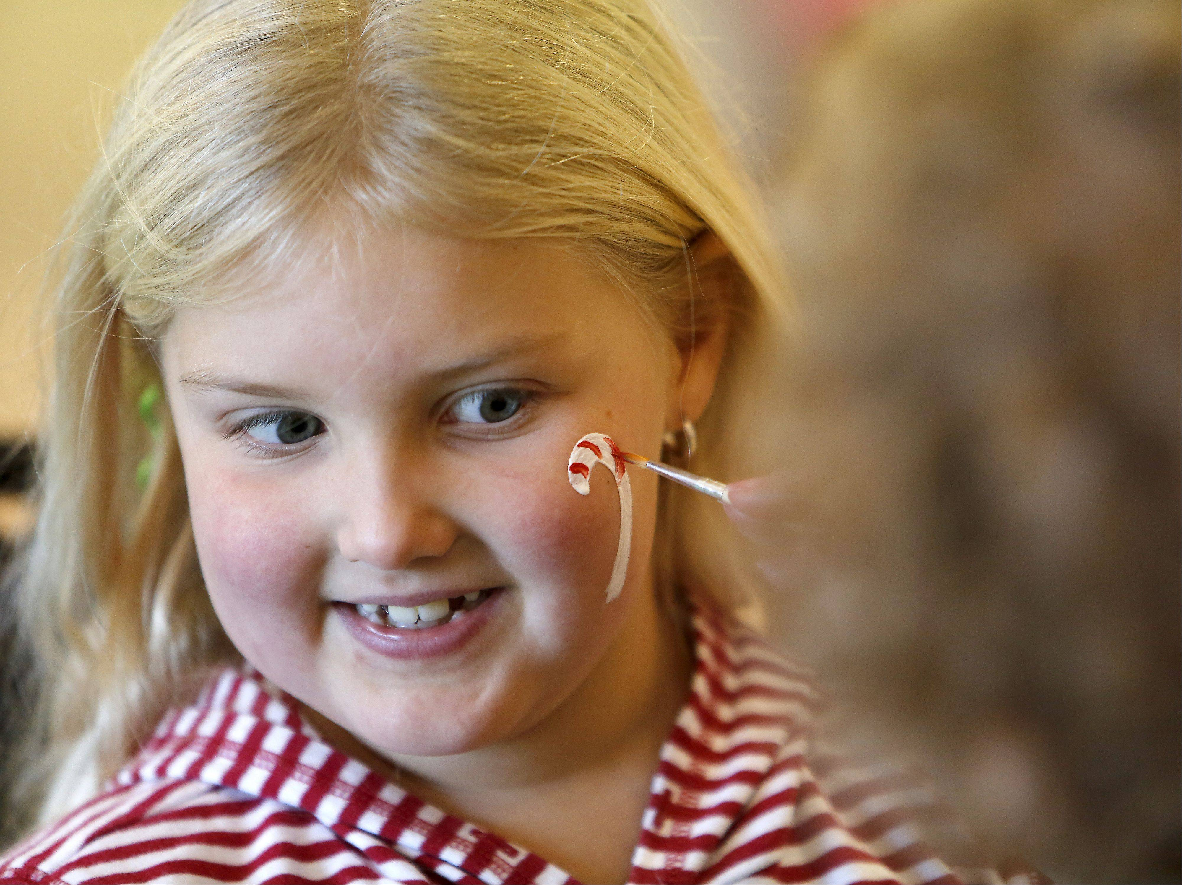 Olivia Barnes, 6, of Elburn gets a candy cane painted on her face during the Kiwanis of Campton Hills holiday kickoff party Saturday.