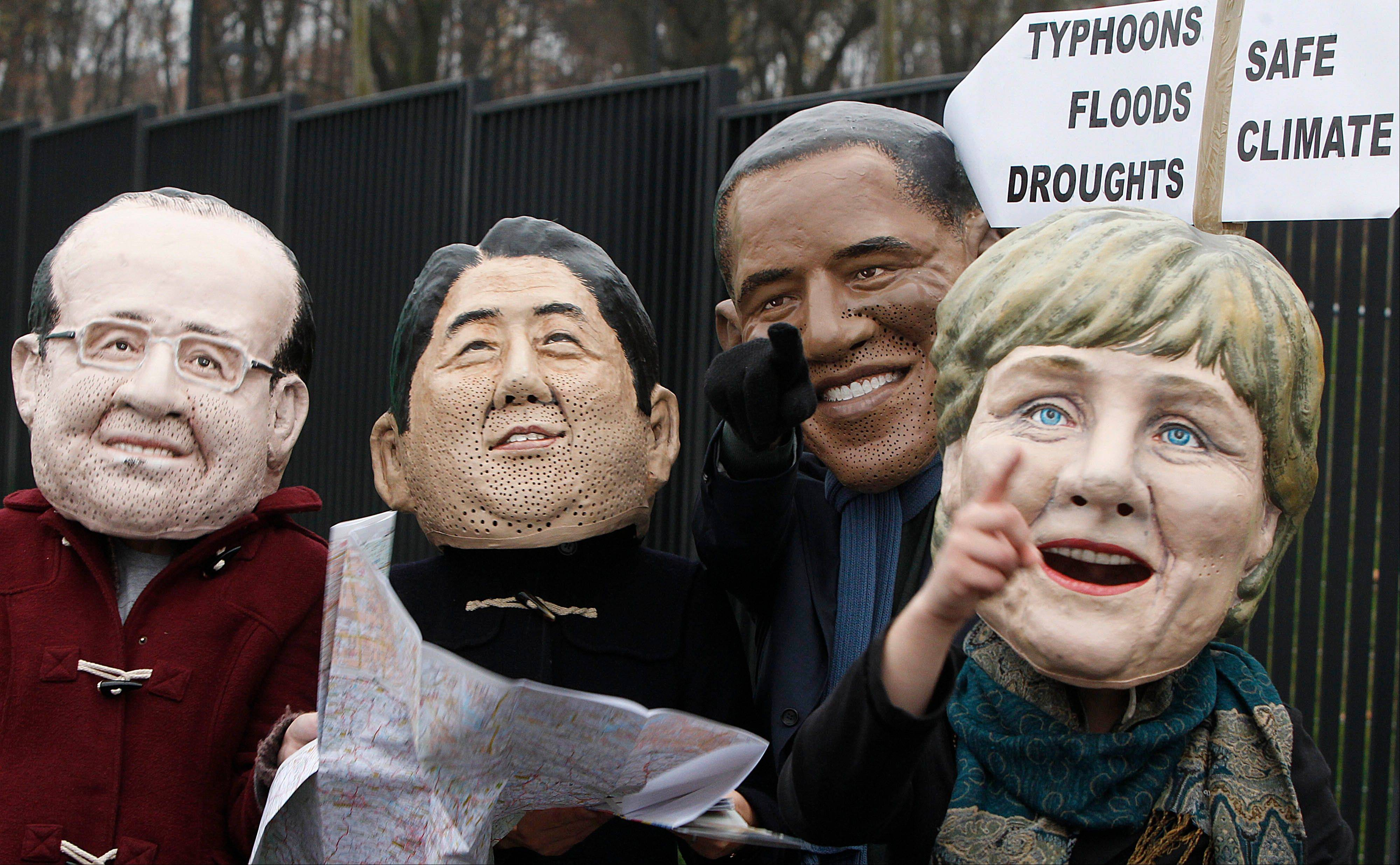 Climate activists protest Friday, acting in the role world leaders, in front of the U.N. climate change conference at the National Stadium in Warsaw, Poland. They are dressed as: French President Francois Hollande, Japan�s Prime Minister Shinzo Abe, U.S. President Barack Obama and German Chancellor Angela Merkel.