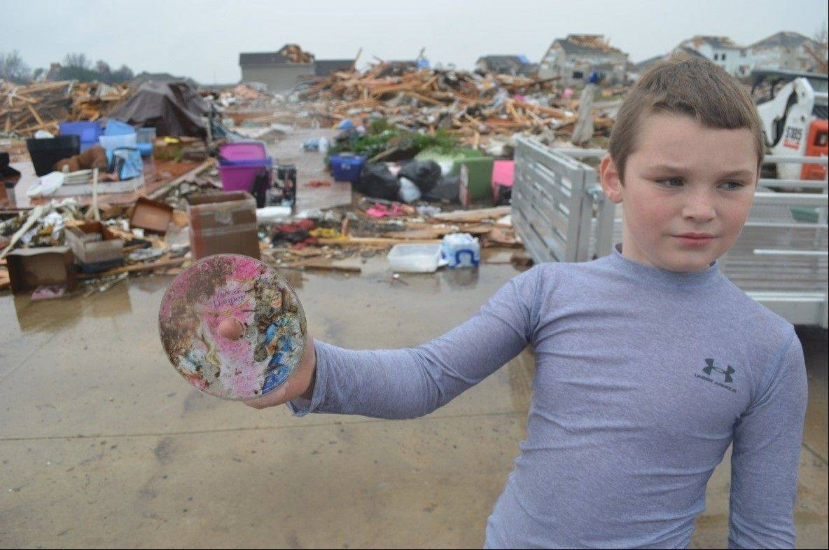 Sam Buckman, 10, of Elgin, went with his family to Washington, Ill. this week to drop off supplies and $25,000 in gift cards to tornado survivors. Here, he stands in front of the devastation and holds up a DVD he found in the wreckage.