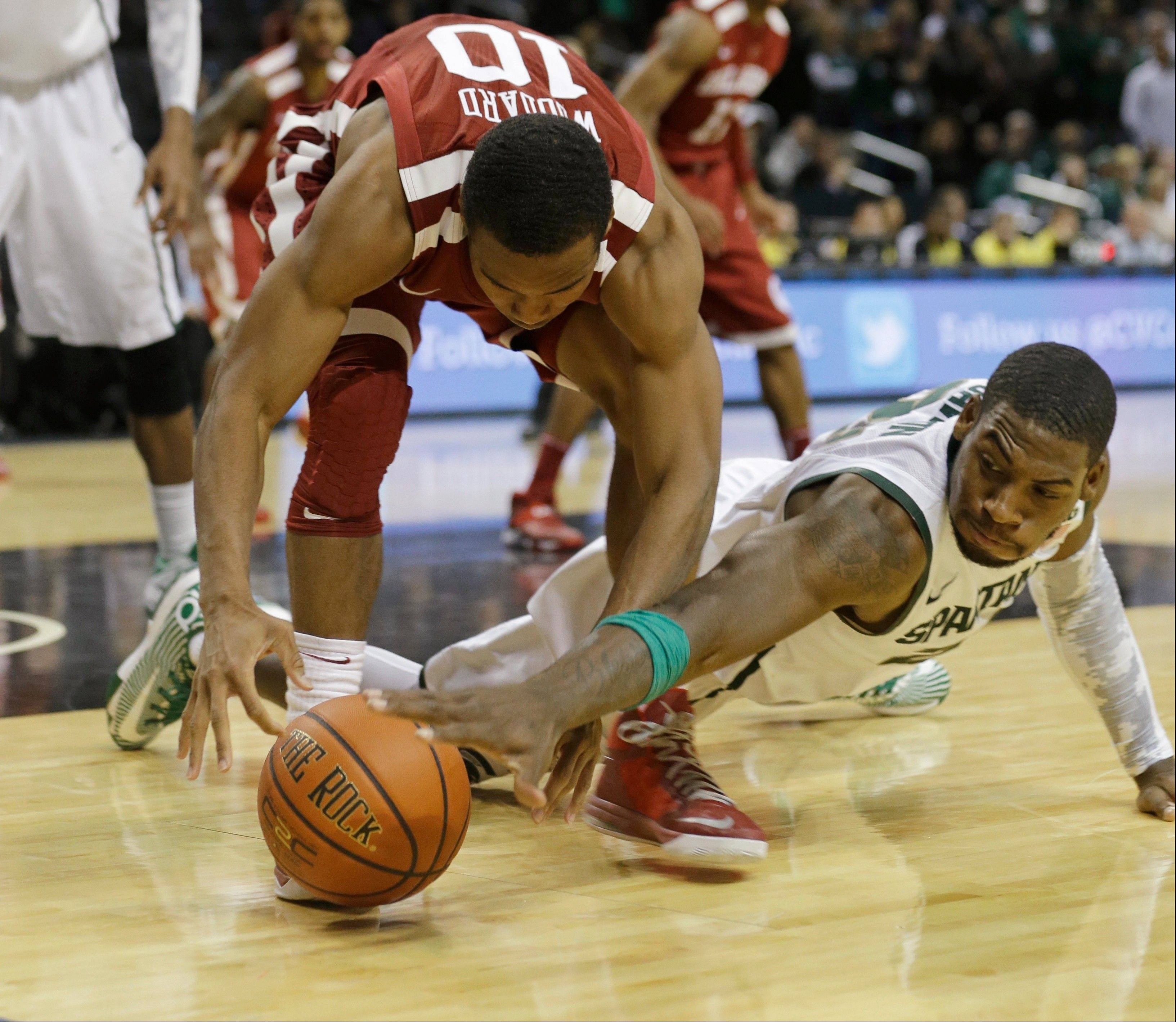Michigan State�s Branden Dawson, right, and Oklahoma�s Jordan Woodard fight for control of the ball during the second half of the championship game in the Coaches vs. Cancer Classic on Saturday in New York. Michigan State won 87-76.
