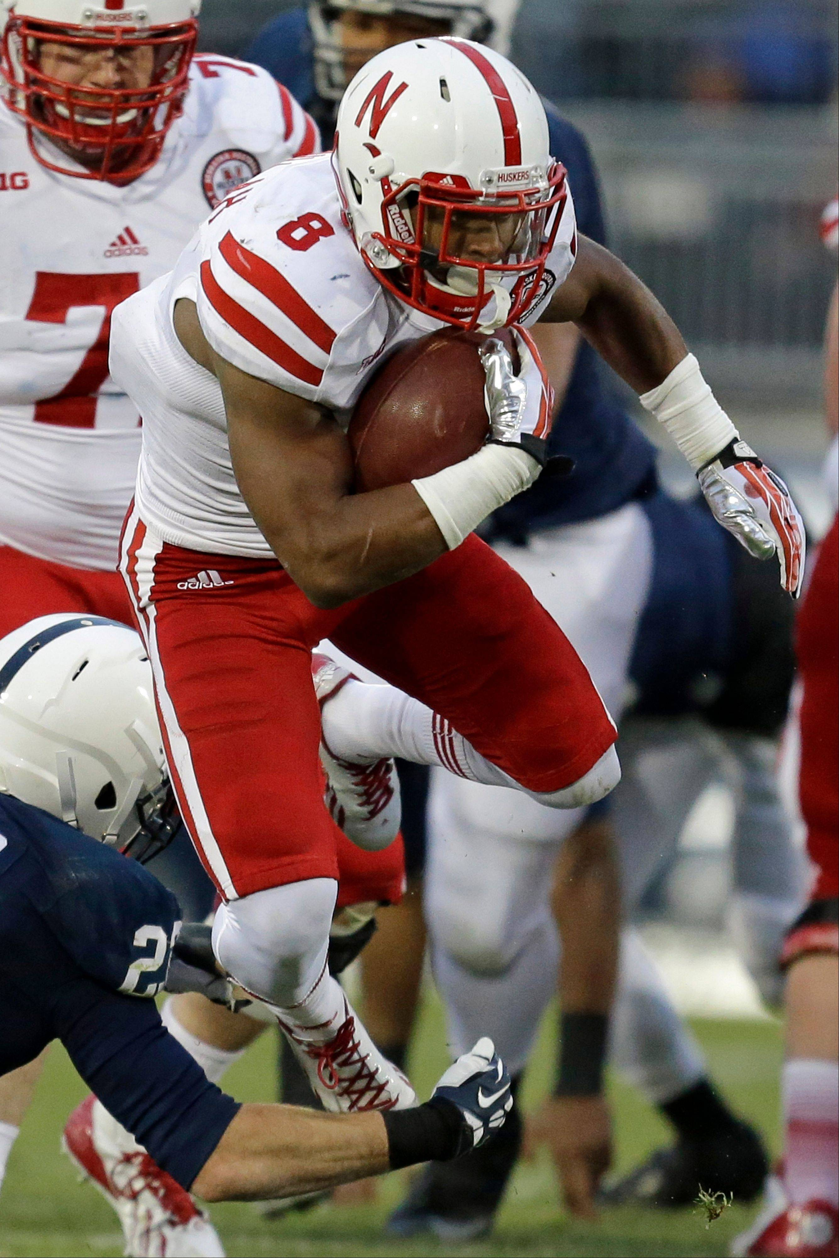 Nebraska running back Ameer Abdullah is tripped up by Penn State safety Ryan Keiser during the second quarter of Saturday�s game in State College, Pa.