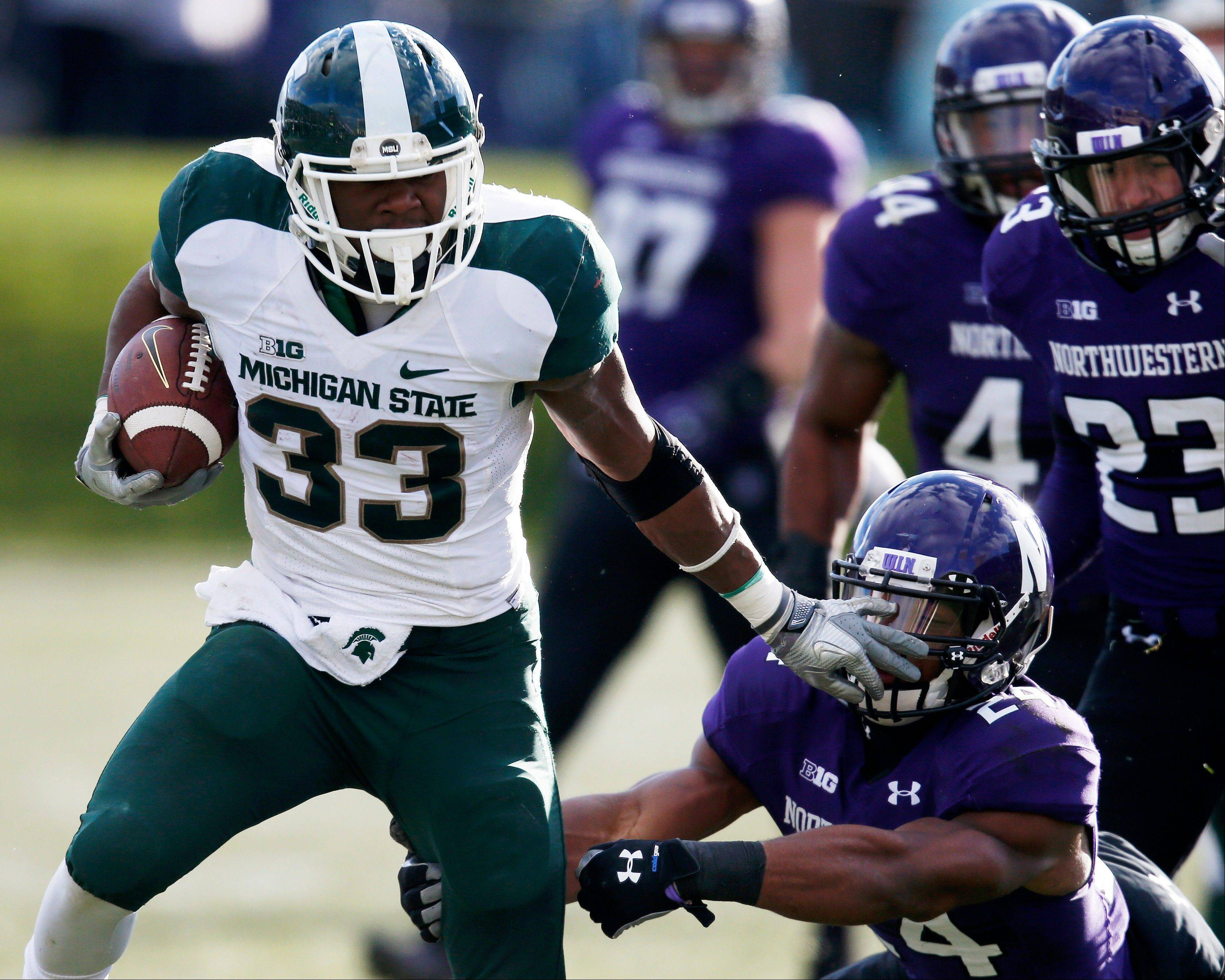 Michigan State running back Jeremy Langford (33) shakes off Northwestern safety Ibraheim Campbell (24) on a touchdown scoring run during the second half of an NCAA football game on Saturday, Nov. 23, 2013, in Evanston, Ill. (AP Photo/Andrew A. Nelles)