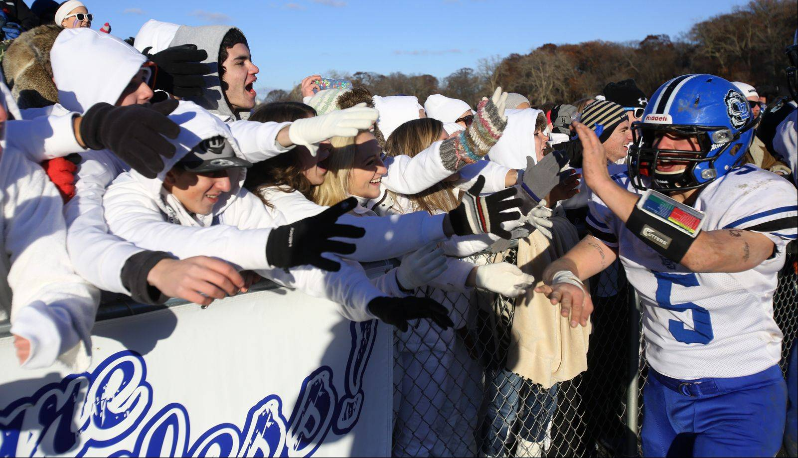 Lake Zurich's Sam Walstrum high fives fans following th Bears' 16-7 Class 7A semifinal playoff win in Glen Ellyn Saturday.