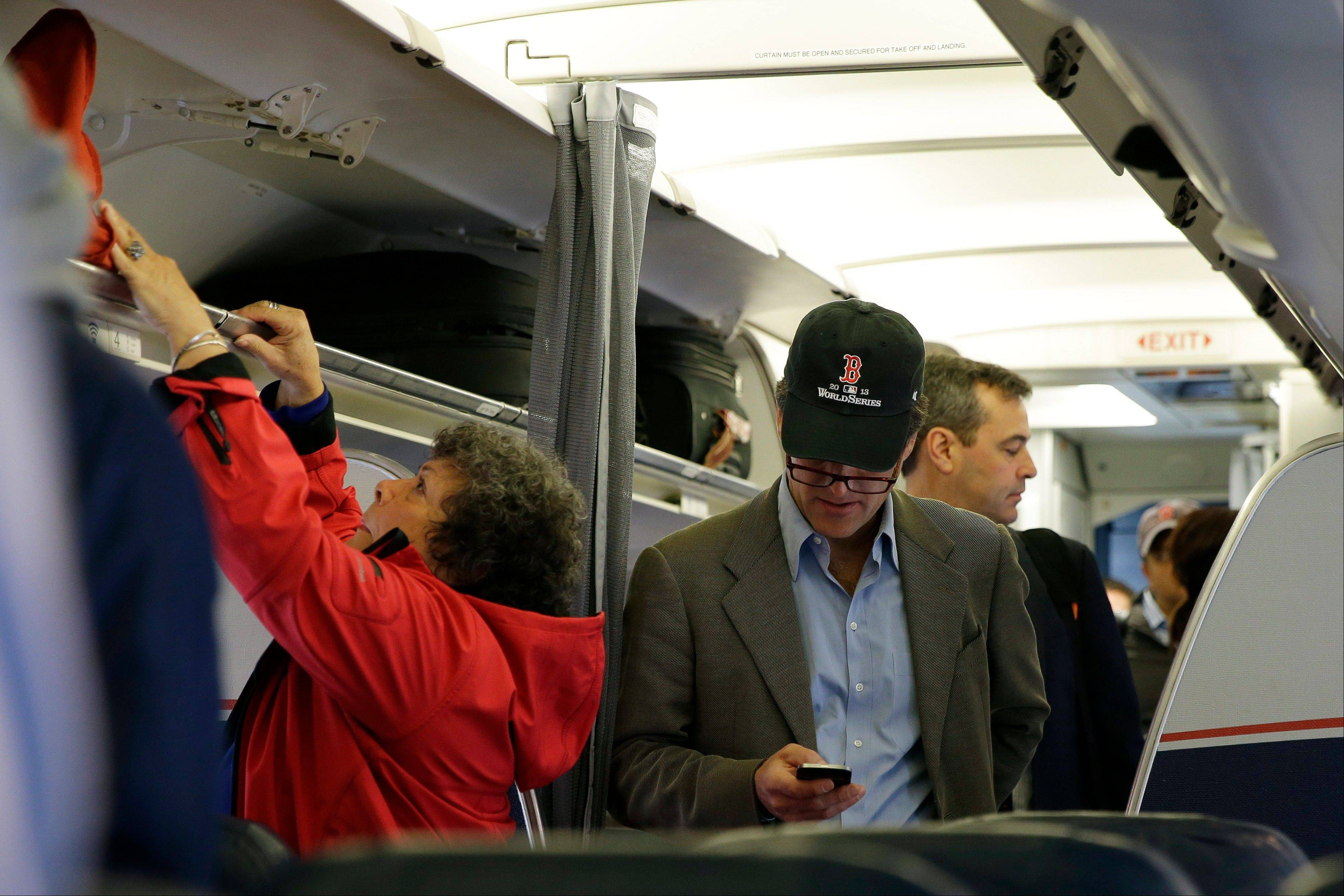 A passenger checks his cell phone while boarding a flight, in Boston.