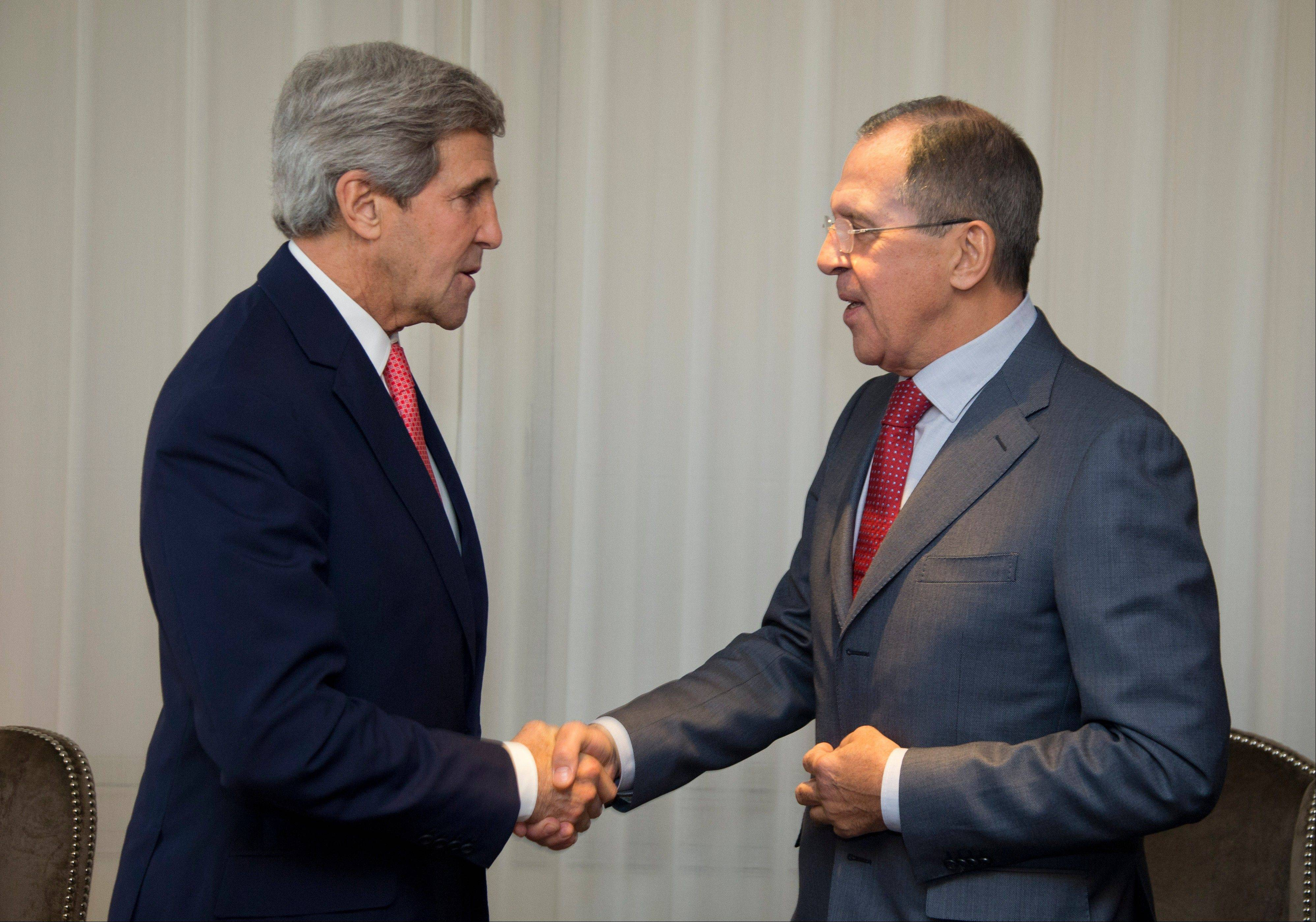 U.S. Secretary of State John Kerry, left and Russia's Foreign Minister Sergei Lavrov shake hands, during a photo opportunity, prior to their meeting Saturday in Geneva, Switzerland.