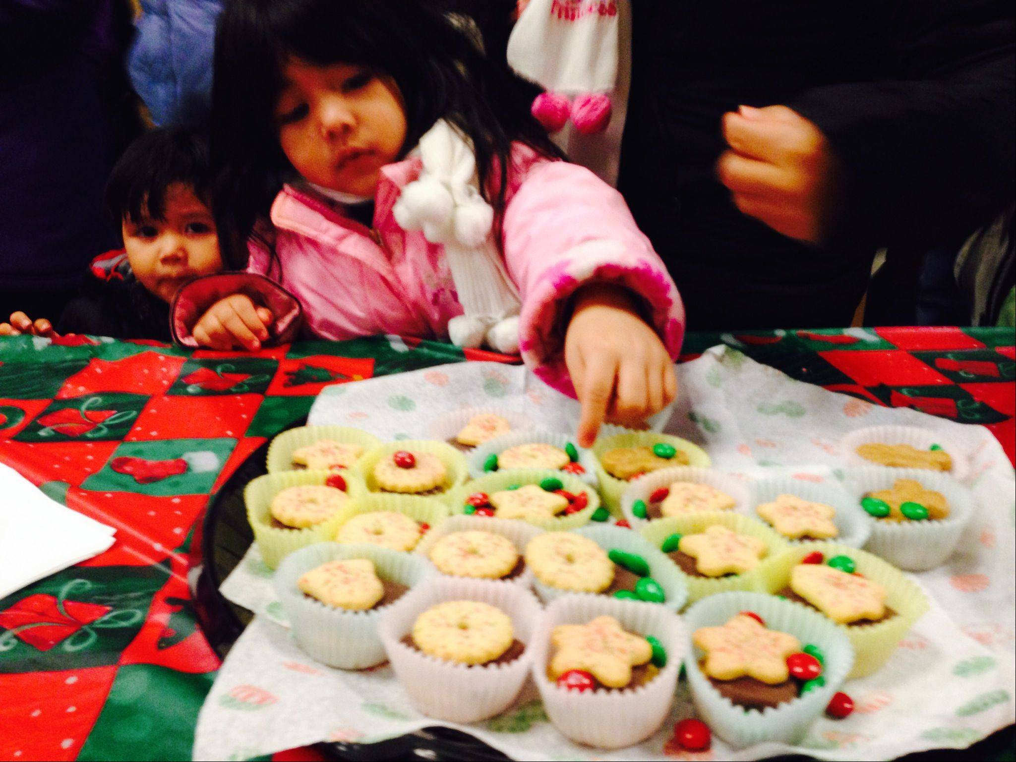 Angeles Zamorano, 4, of Hoffman Estates selects a cookie Saturday at the village's holiday celebration.