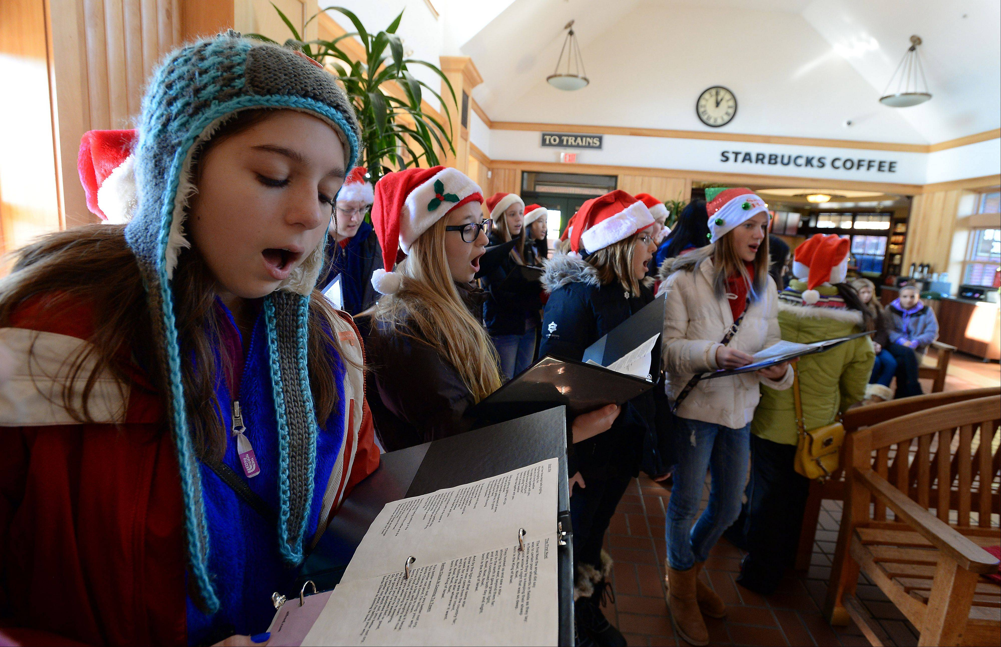 "Elena Mandarino, 13, of the Walter R. Sundling Junior High School chorus belts out the songs, ""The First Noel,"" ""Have Yourself a Merry Little Christmas"" and ""Here Comes Santa Claus"" with the rest of her singing mates Saturday at the Palatine train station as part of Palatine's Family Fun Day."
