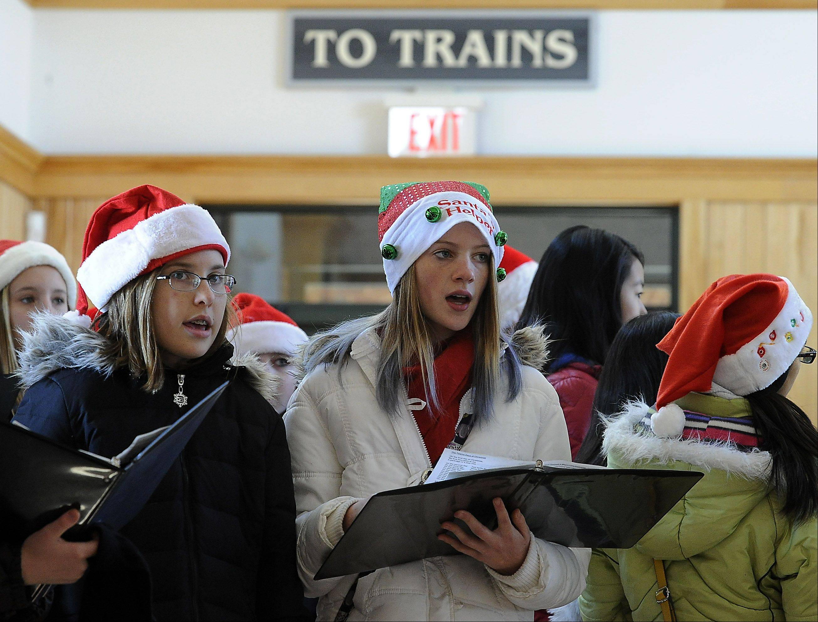 "Bronte Phipps, 12, of the Walter R. Sundling Junior High School chorus, aka Santa's little helper, belts out the song ""The First Noel"" with the rest of her singing mates Saturday at the Palatine train station as part of Palatine's Family Fun Day."
